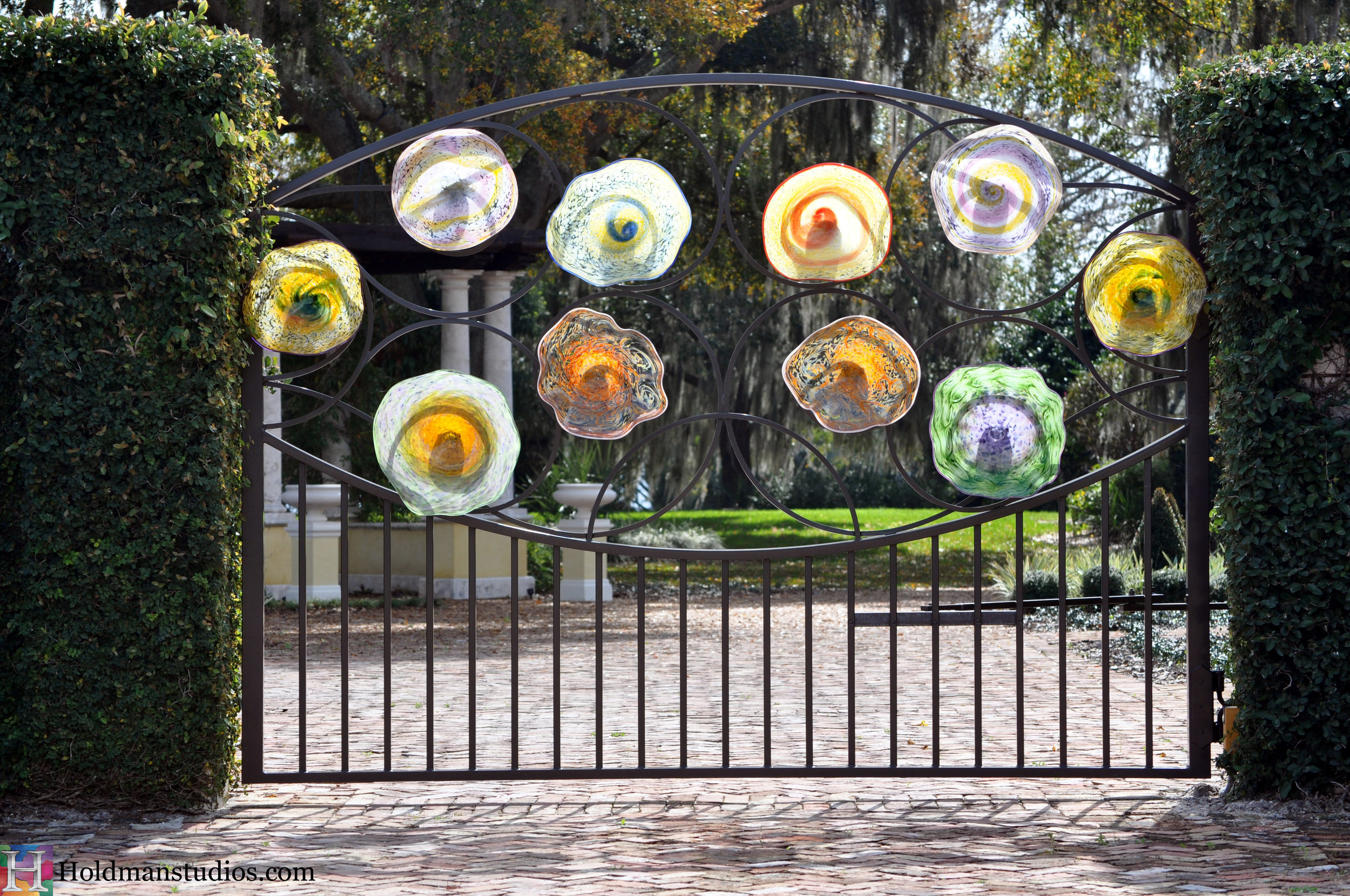Hand blown platters on fence gate. Created by artists under the direction of Tom Holdman at Holdman Studios.