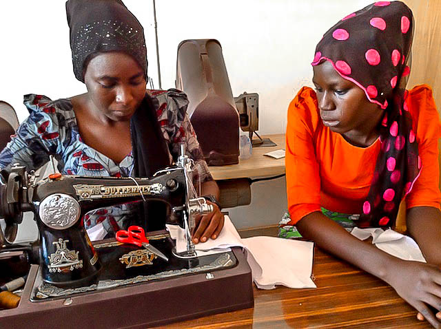 Mariam at fashion school watching how her collegue does the sewing.jpg