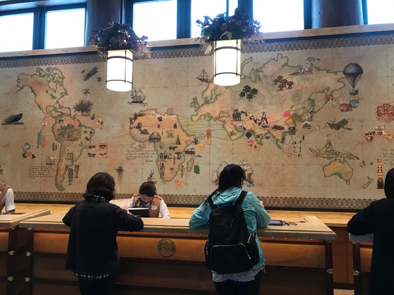 The check-in desk has a beautiful world map behind it!