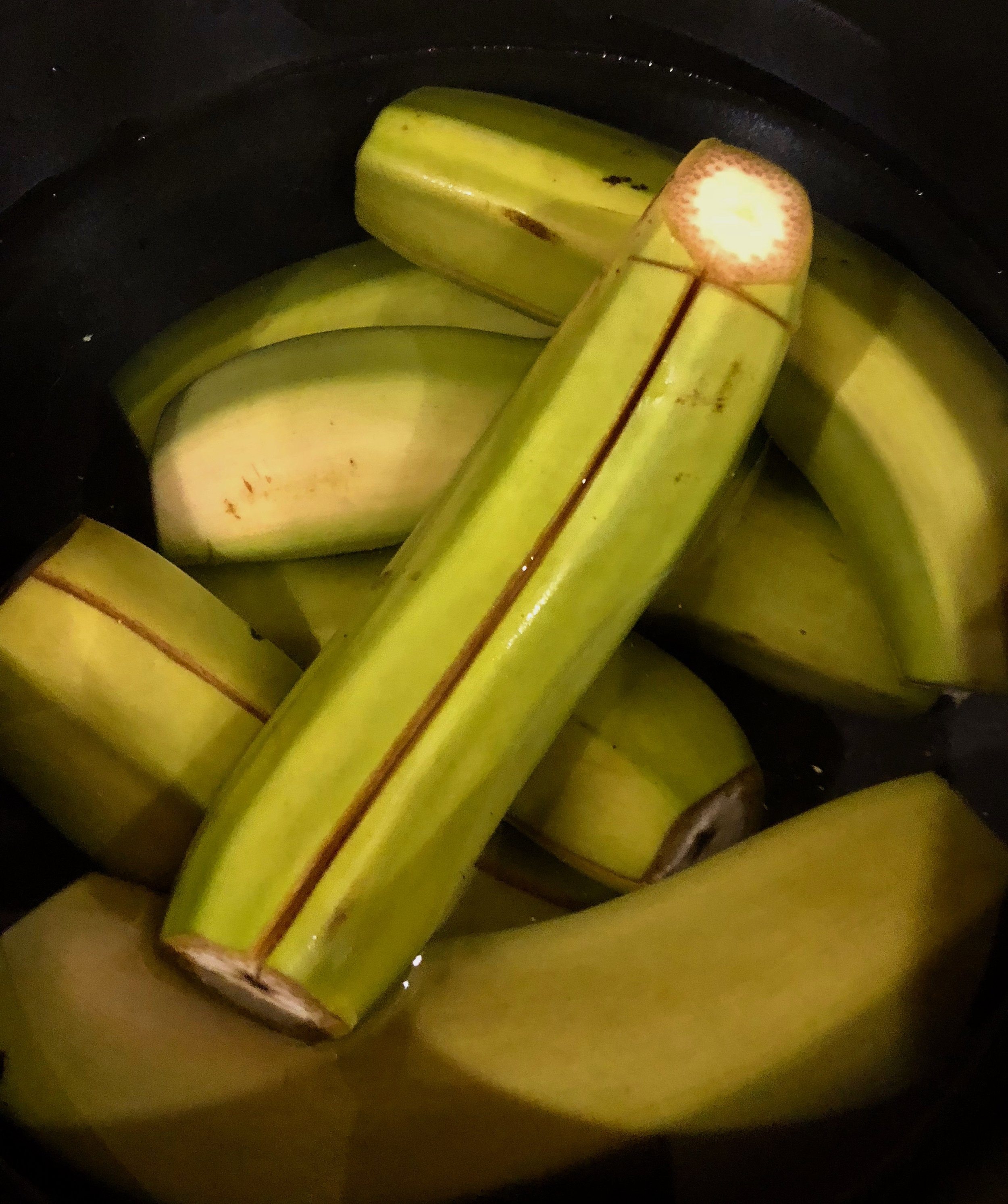 To prepare bananas before boiling, cut off both ends of the bananas and score the skin down the middle.