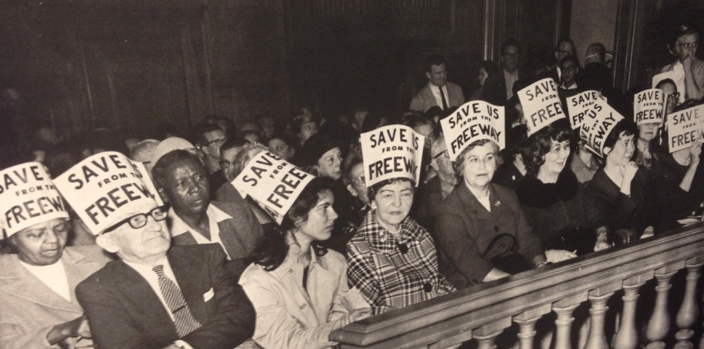 Citizens crowd into City Hall wearing signs on their heads to express their opposition to the freeways being erected all over San Francisco. Source: San Francisco History Center, San Francisco Public Library.