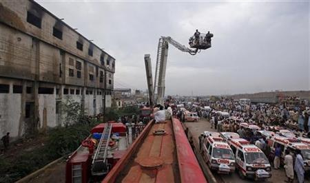 Ambulances and fire brigade vehicles outside a building, after a fire at a garment factory in Karachi September 12, 2012 (a day following the eruption).  PHOTO: REUTERS/Akhtar Soomro