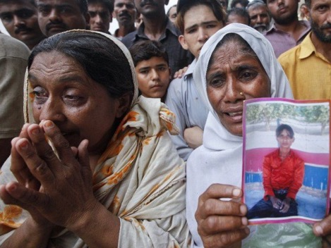 """A woman holds a portrait of her son while waiting with others to identify his body.  PHOTO: REUTERS  """"If my son does not return, I will commit suicide in front of the factory,"""" one woman shouted before news cameras as relatives tried to console her [ SOURCE: NY Times ]"""