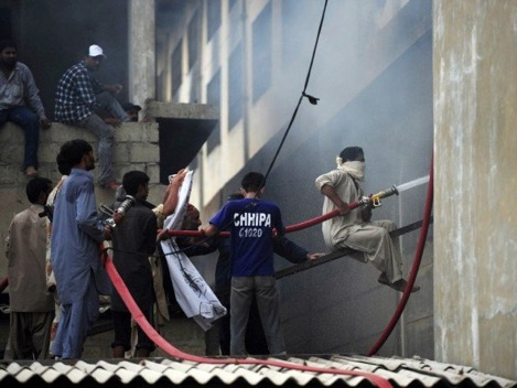 Firefighters battling the fire following day.  PHOTO: AFP  Note the lack of firefighting gear of the Fire Brigade staff.