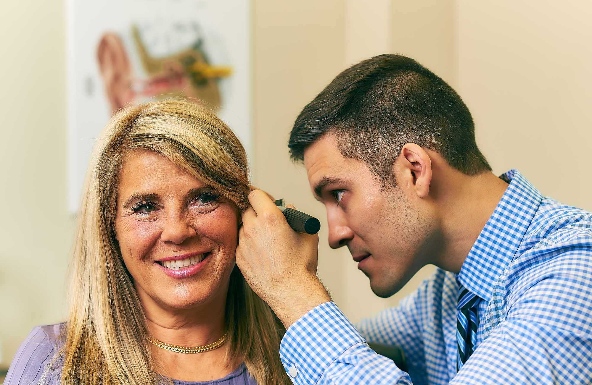 Neil Fine, Ottawa Audiologist, checking a happy patients rigth ear.