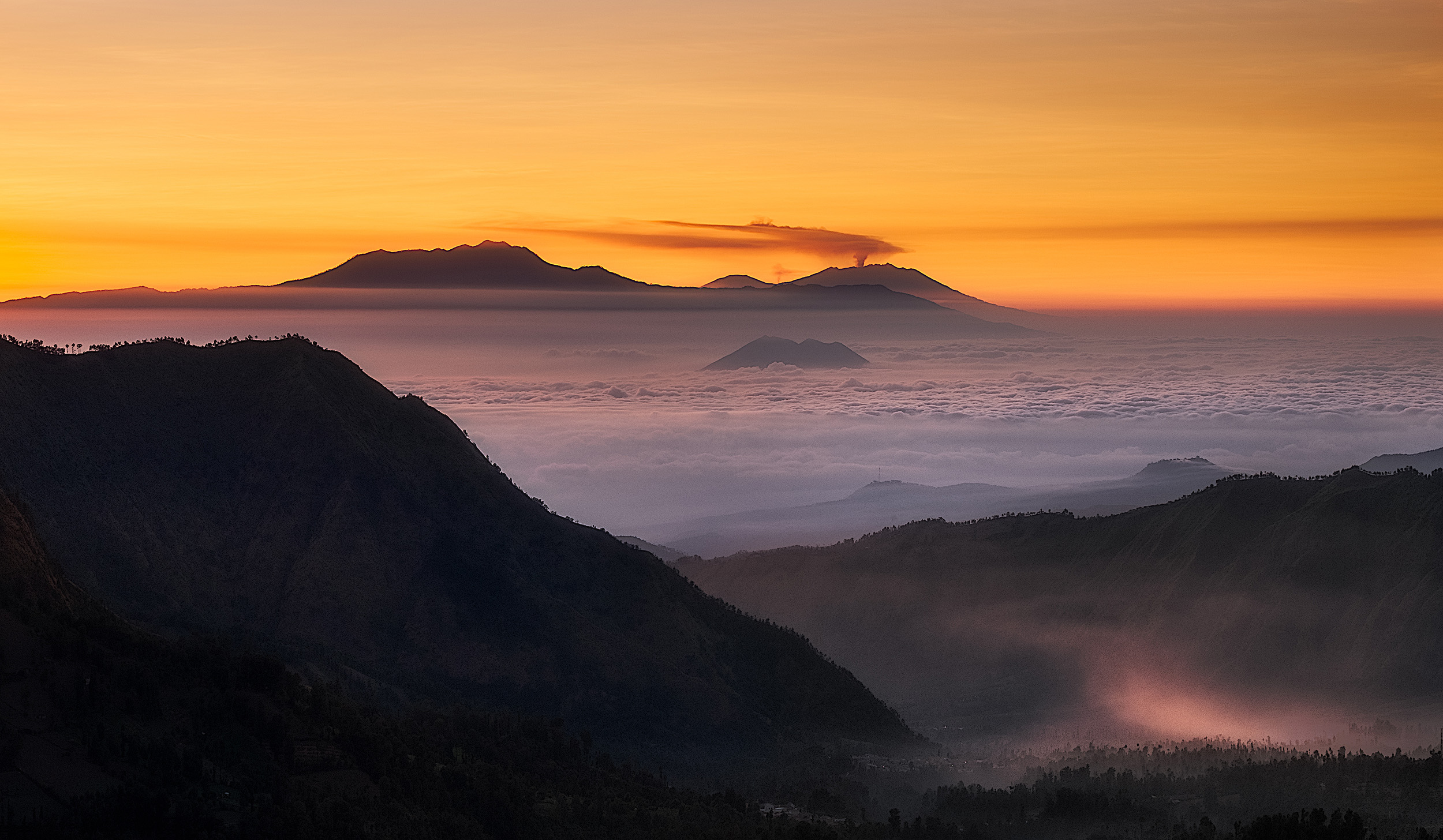 East Java Sunrise   Looking east from Penanjakan on the Bromo crater as the sun rises across the volcanos of eastern Java. The small peak surrounded by cloud is the Gunung Lembongan and behind that and to the left is the 3000m Gunung Argapura. Behind that is the smoking Gunung Raung, the volcano that disrupted so many flights to and from Bali in August and September 2015. It's about 120km away from where we were standing.