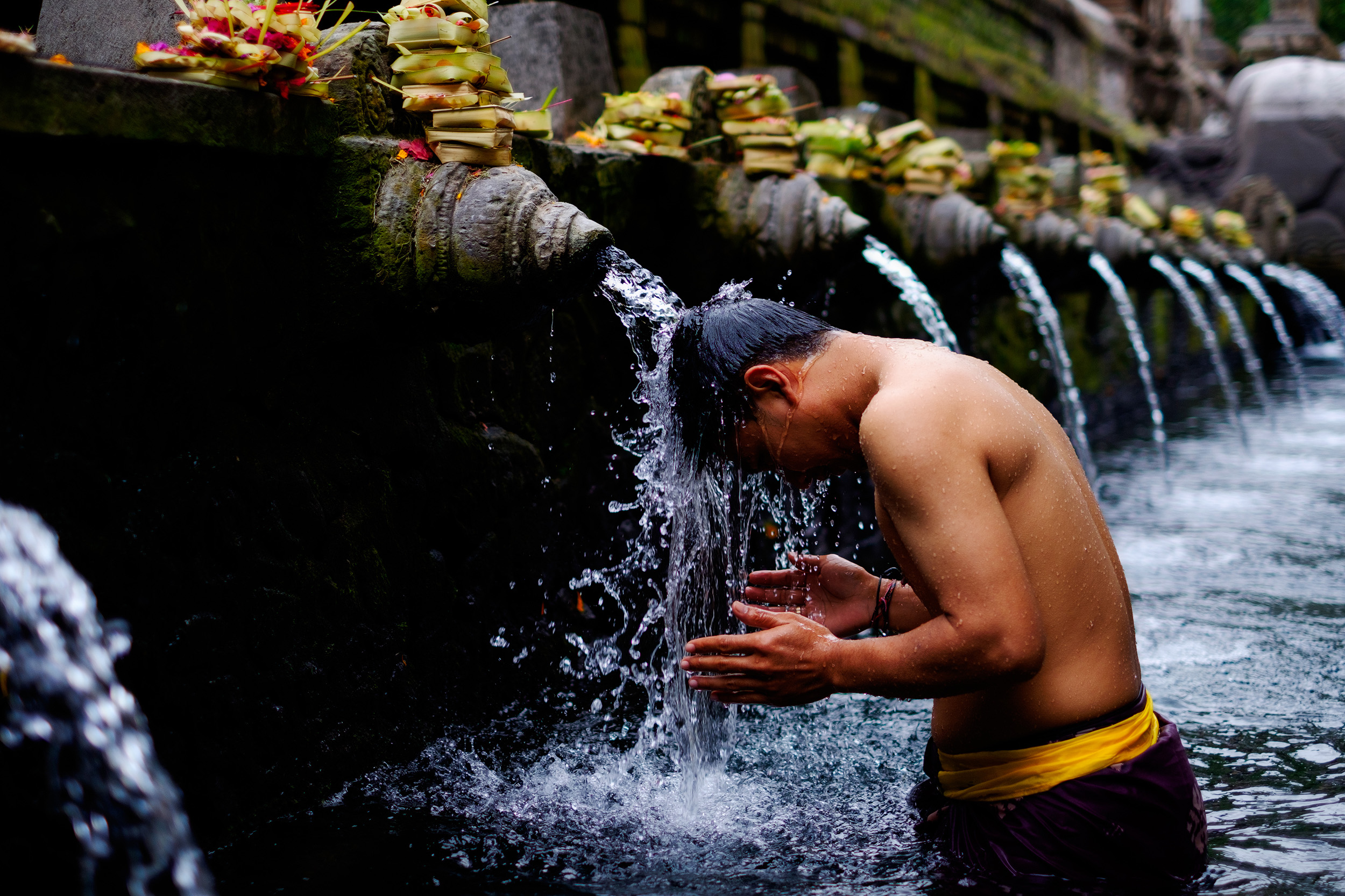 Tirta Empul   People travel from all over Bali to bathe and sanctify themselves in the spiritual waters of Tirta Empul. According to legend, the God Indra pierced the earth to create a fountain of healing waters after the land had been poisoned. People bathe and leave offerings on top of each fountain as they work there way down the pool.  It's a wonderful place to spend a few hours in the morning. I had to put on a sarong and get into the water to get this shot.