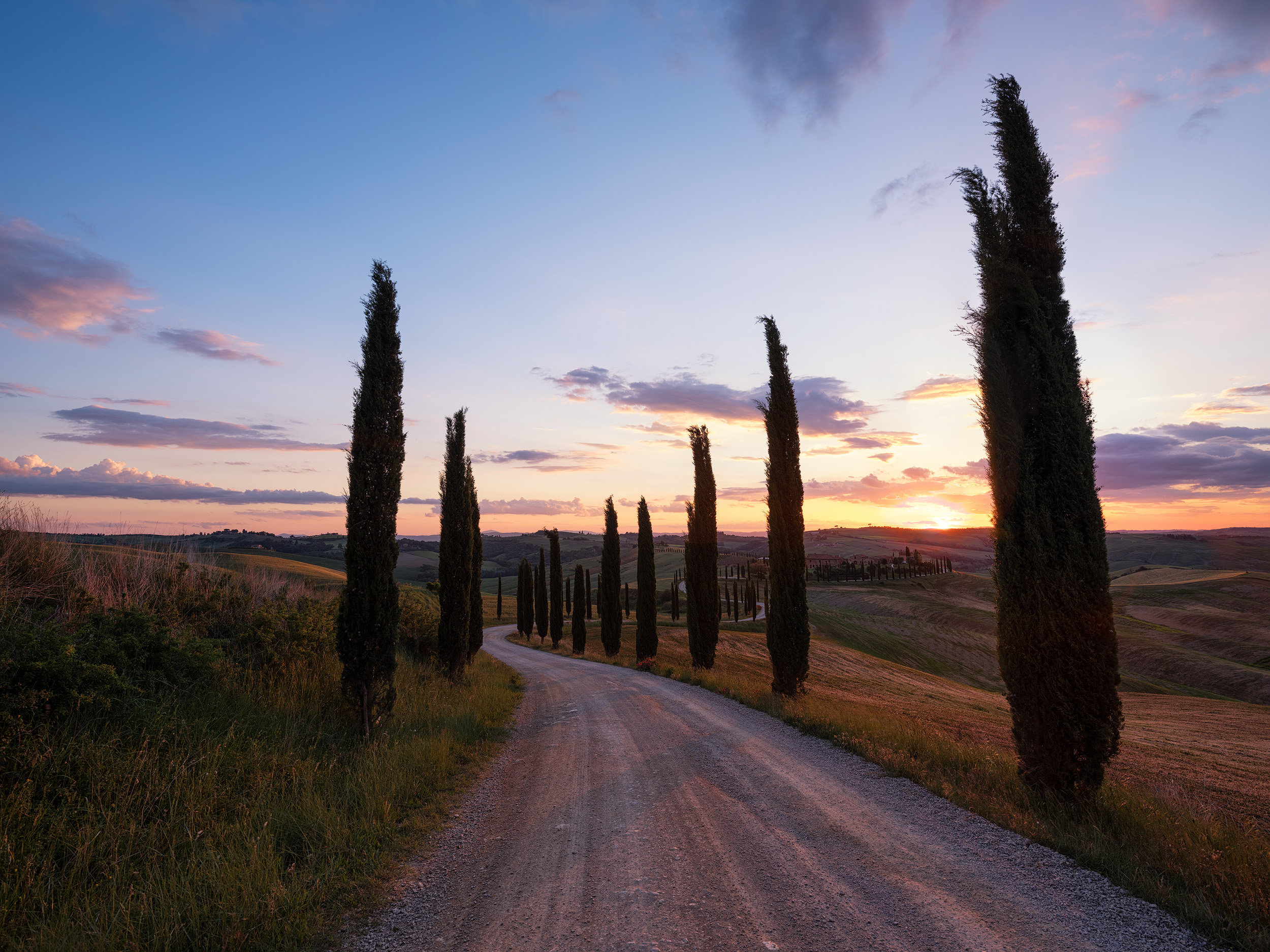 Baccaleno   A winding, cypress lined road across rolling hills to a stone farmhouse. It can only be Tuscany. This image was taken in Crete Senesi, south of Siena.