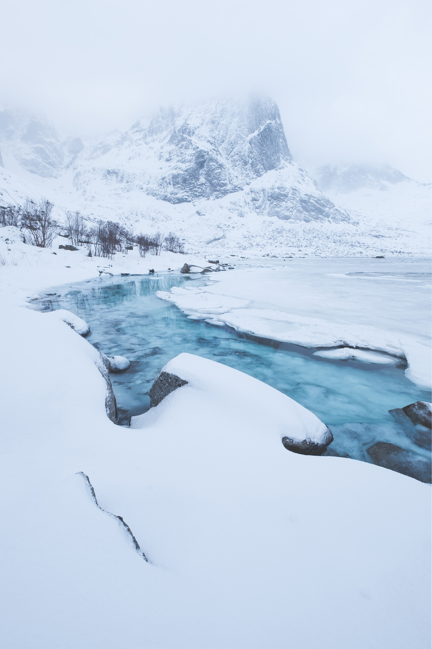 White & Blue   The clear blue water of an almost frozen fjord surrounded by the a fresh snowfall in the Lofoten Islands, Norway