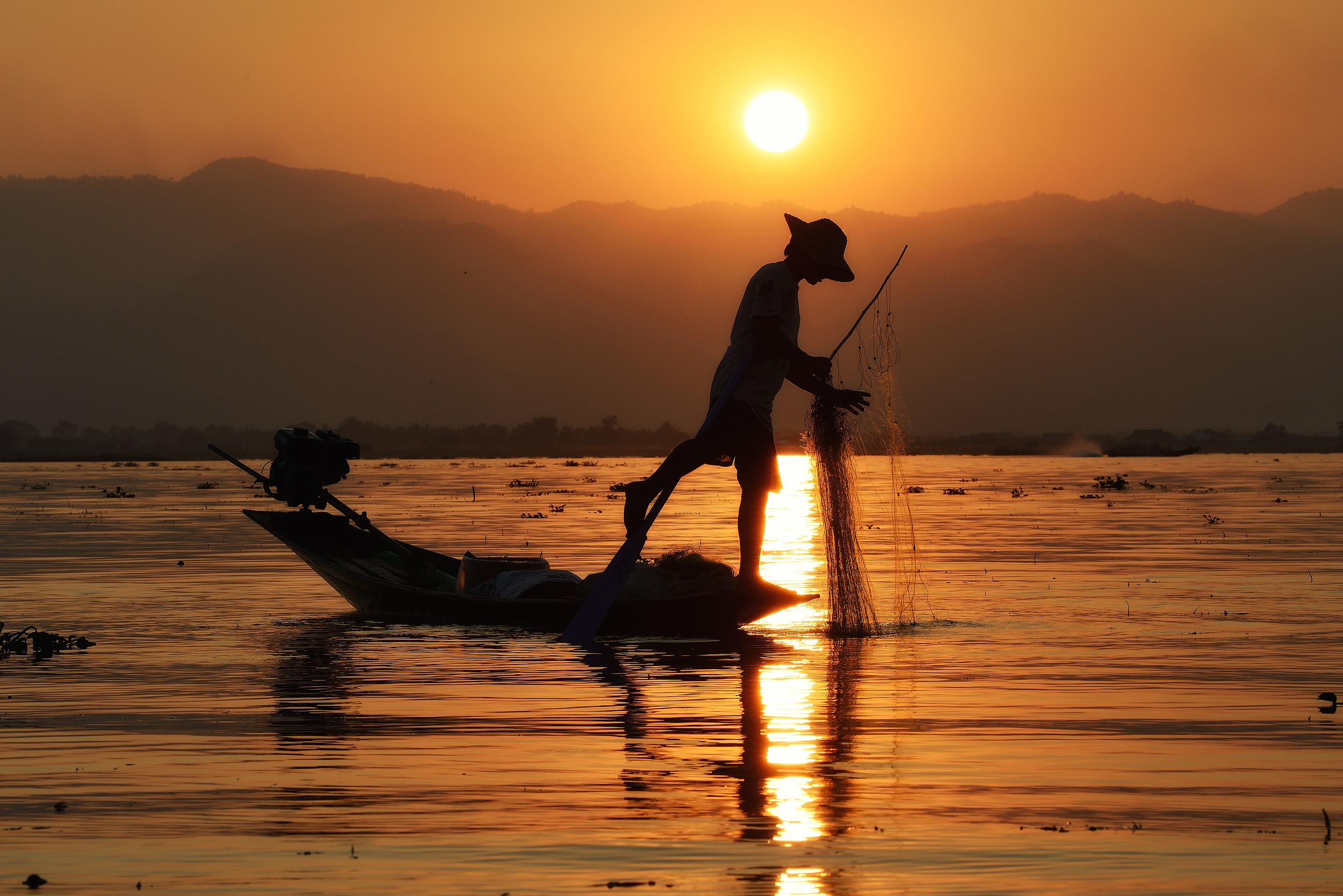 Last light at Inle   A fishermen tends his nets as the sun sets at Lake Inle.