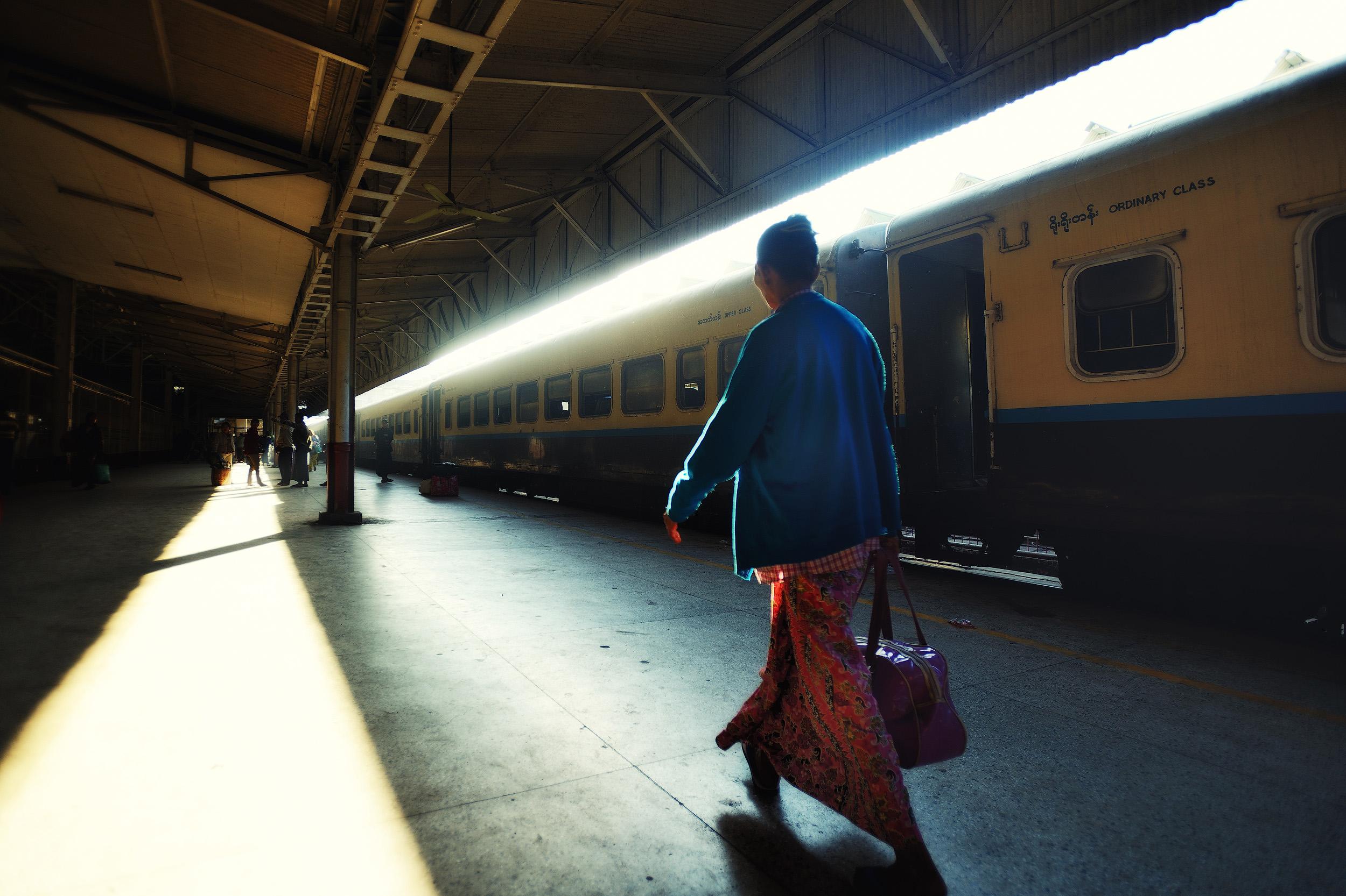 Yangon Train Station   A woman hurries along the platform just after dawn at Yangon central train station