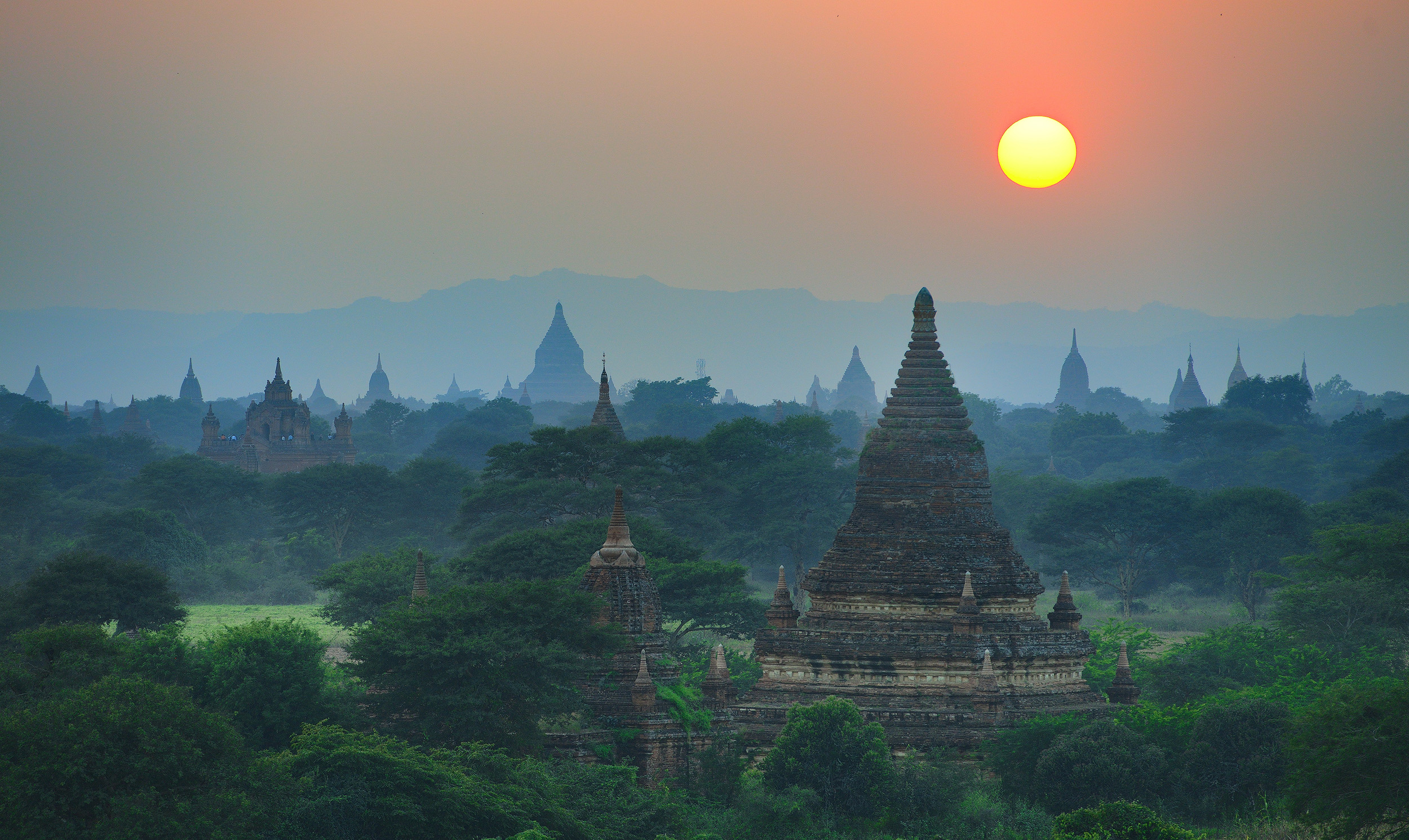 Bagan Sunset   Sunrise is really the best time to photograph Bagan. There's usually a layer of mist on the plain, there are balloons in the sky, and you can find temple tops that are really quiet to set up and shoot from. However, as we were passing this temple on our bicycles as the sun got lower in the sky I decided I may as well have a walk up the steps and watch the sunset….and of course, as soon as I got there I couldn't resist taking a couple of frames. So this is the view from the top of Buledi temple as the sun sets in the west