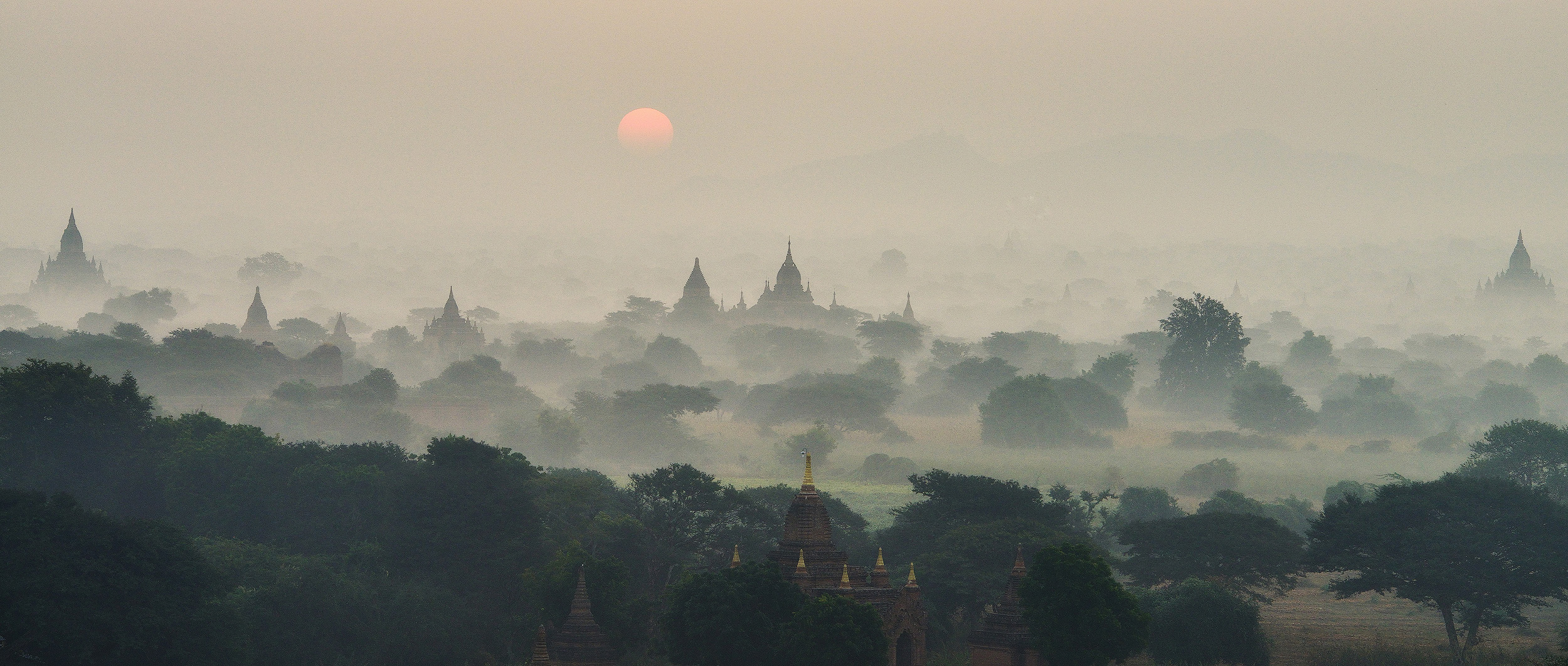 Temple Sunrise   Another image from a wonderful sunrise at the temples of Bagan. The plain of Bagan has around 2000 temples scattered over a few square kilometers, and in the morning mist rolls access the plain and the neighboring River Ayerwaddy, making each temple appear like an individual island in the fog. It really is a remarkable scene.