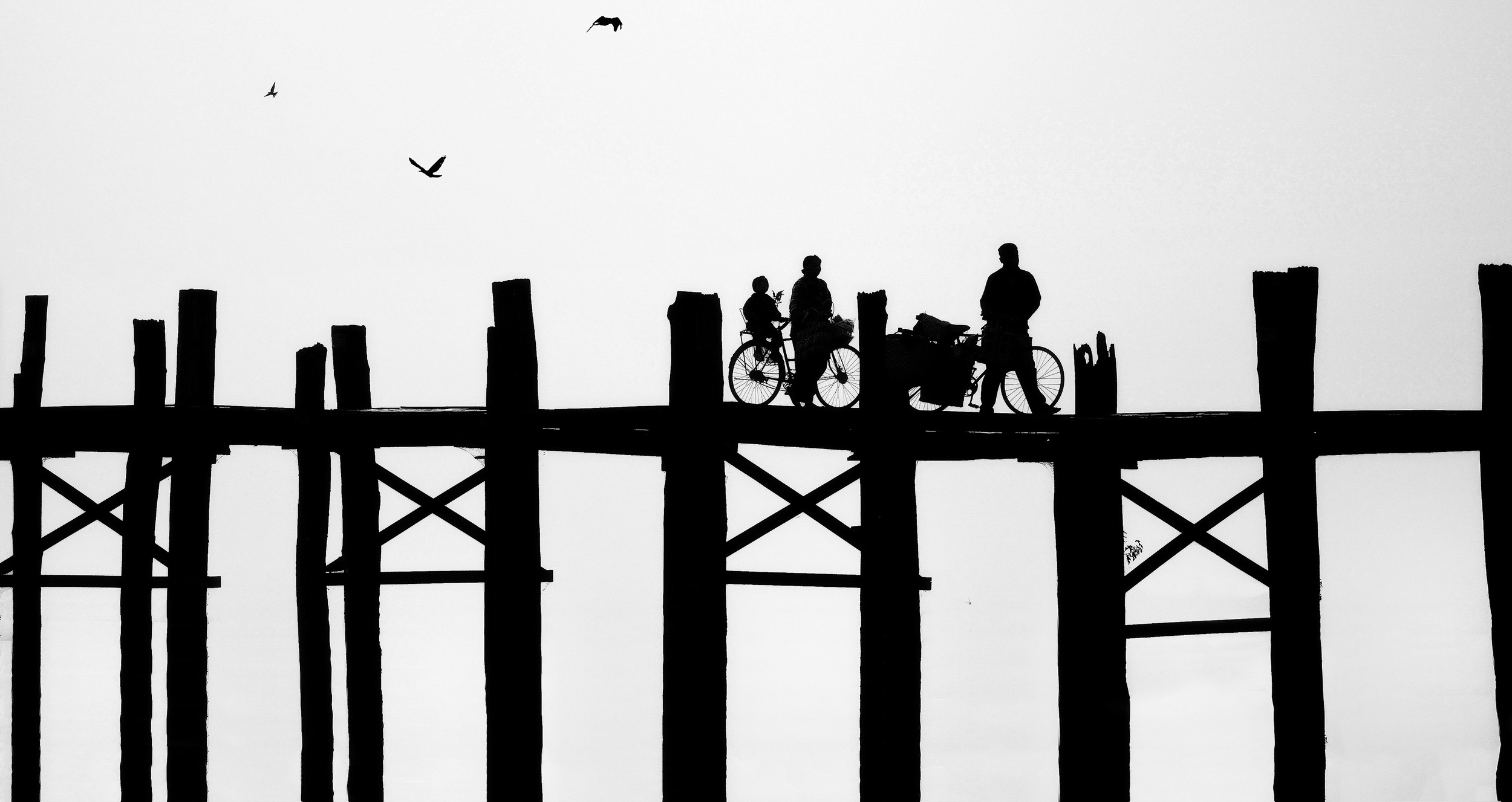 U Bein Bridge   The U Bein teak bridge across Tuang Tha Man lake in Amarapura, Mandalay, is the longest teak bridge in the world. Over a kilometer long and more than 150 years old, it spans the large lake and is an incredibly busy passageway connecting the two banks. I was there for dawn when it was (just a little) quieter, but even at that time the bridge thronged with people going about their business and monks crossing to get to some of the large monasteries in Amarapura.