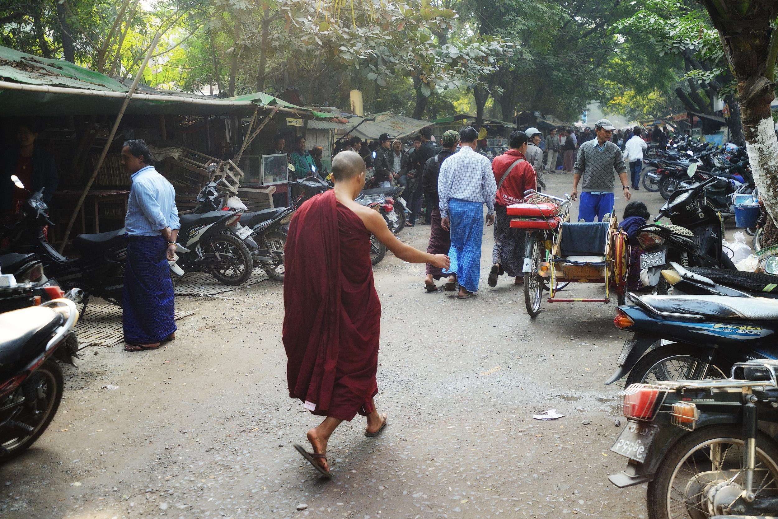 The Jade Market   A monk walks through the hurly burly of the jade market in Mandalay