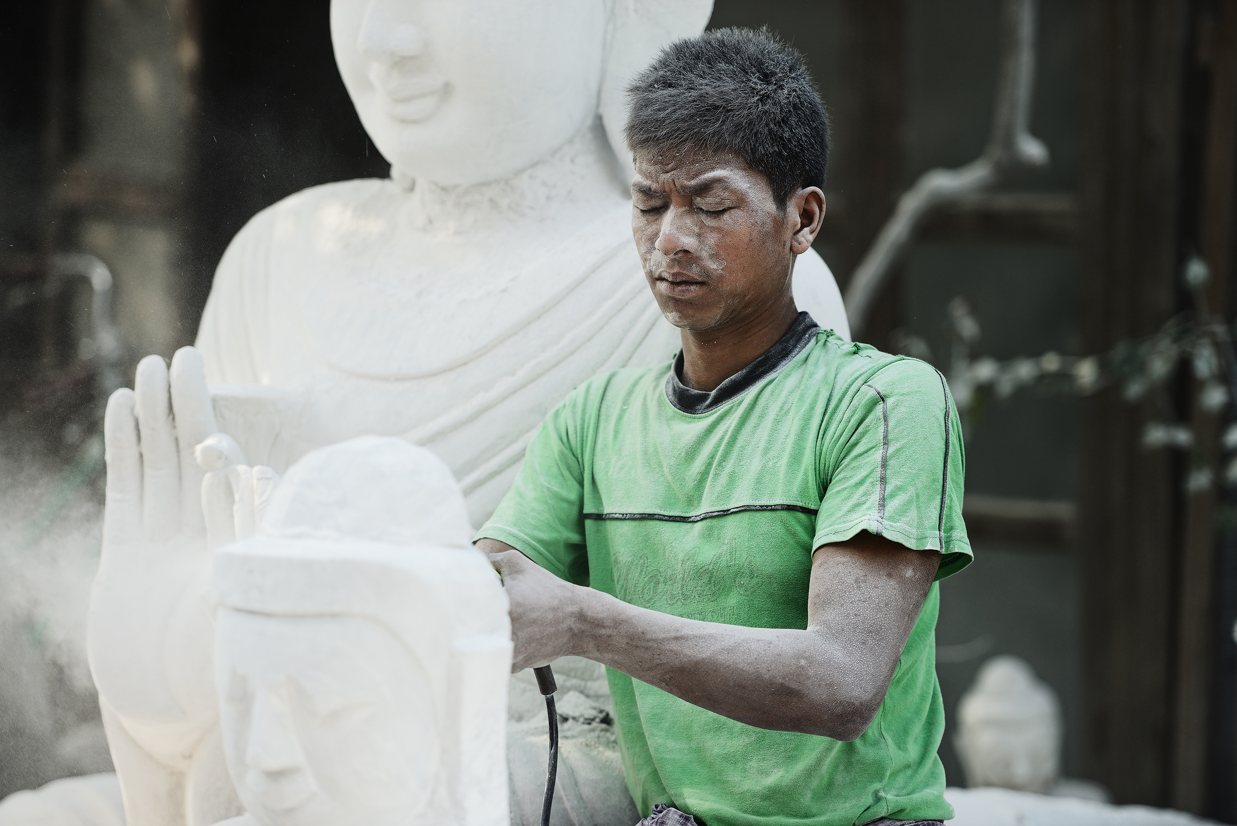 The Stone Carver   Scattered at roadsides throughout Amarapura and Mandalay are lots of stone carvers who shape and carve slabs of stone into buddhas of all shapes and sizes. Watching the carvers work on buddhas in various states of completion is a fascinating process as they hone the statues into their finished forms. It's brutal work and after just a few minutes standing watching you'll feel the dust in your eyes and throat and yet the men here work without goggles or masks breathing the dust all day long, day after day.