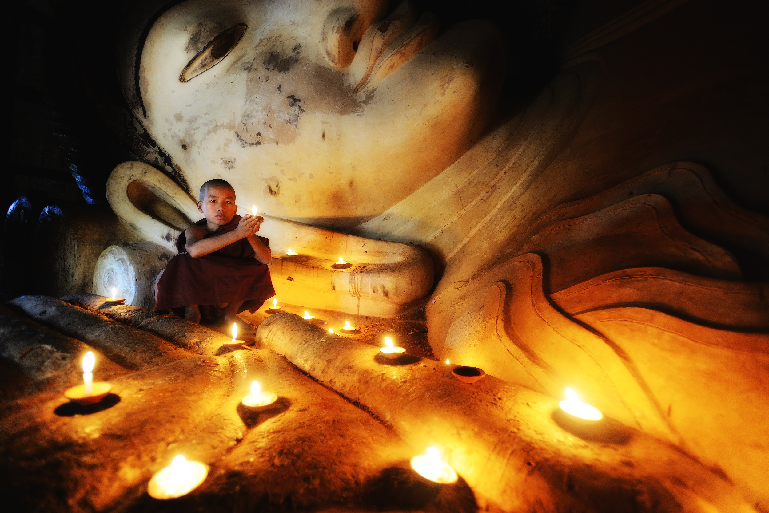 """Prayer   A shot of a novice monk in front of the reclining buddha at Shwesandaw Paya, Bagan. As we entered the tiny building where the buddha is located we came across a photographer shooting this scene. It's not a """"natural"""" scene, as the photographer, who was shooting a book in Burma, had a guide who'd set up the scene for him complete with local novice monks who were carefully posed and lit. The photographer invited me to take a shot of the scene and even though I'm generally not a big fan of contrived posed scenes like this, I wasn't going to decline."""