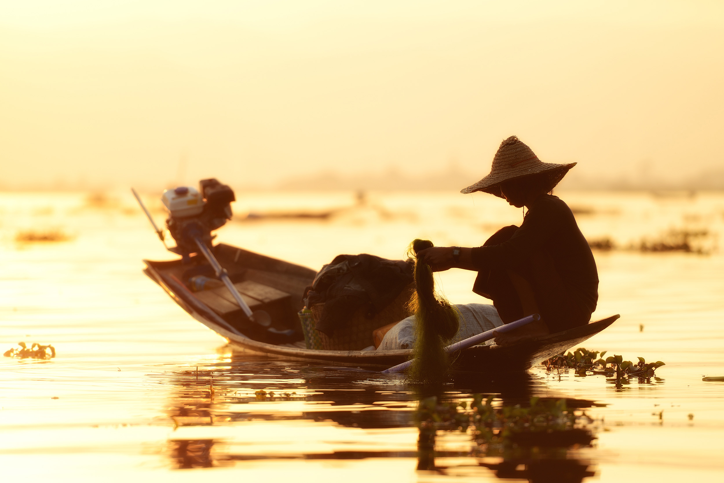 """Lake Inle Fisherman   Lake Inle in the mountains of Shan State, central Burma, is a truly astonishing place. The lake has entire villages set on stilts above the water scattered all over the lake and entire communities and ways of life are centered around the water. Crops are grown in floating gardens, fabrics are produced in large wooden """"factories"""" on stilts, and of course everywhere you go there are fishermen. I took this shot in the very last light of day before the sun dipped behind the mountains."""