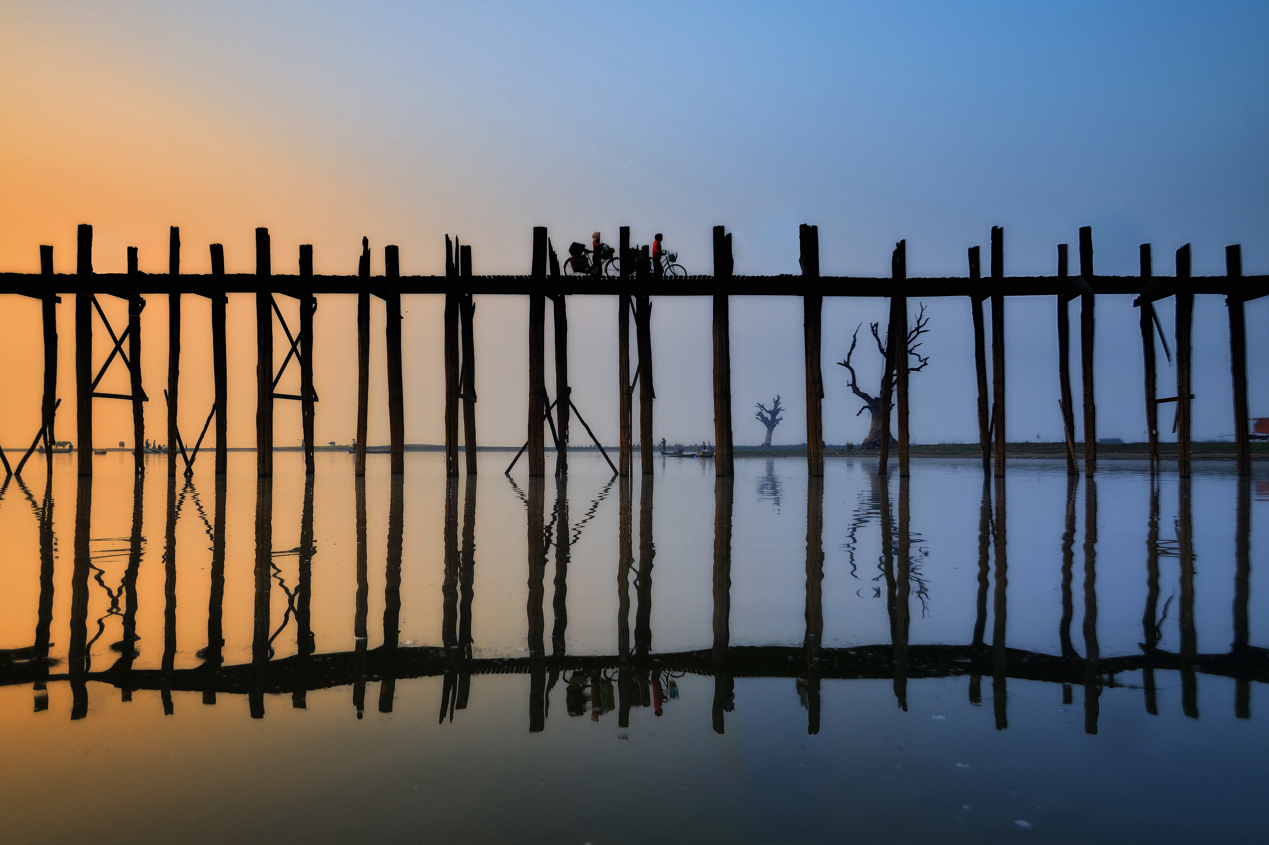 U Bein Reflection   U Bein bridge in Amarapura, southern Mandalay, as the sun burns through the mist at dawn. I set off in a boat when it was still dark and misty and photographed the bridge as it got busier and busier with early morning commuters.