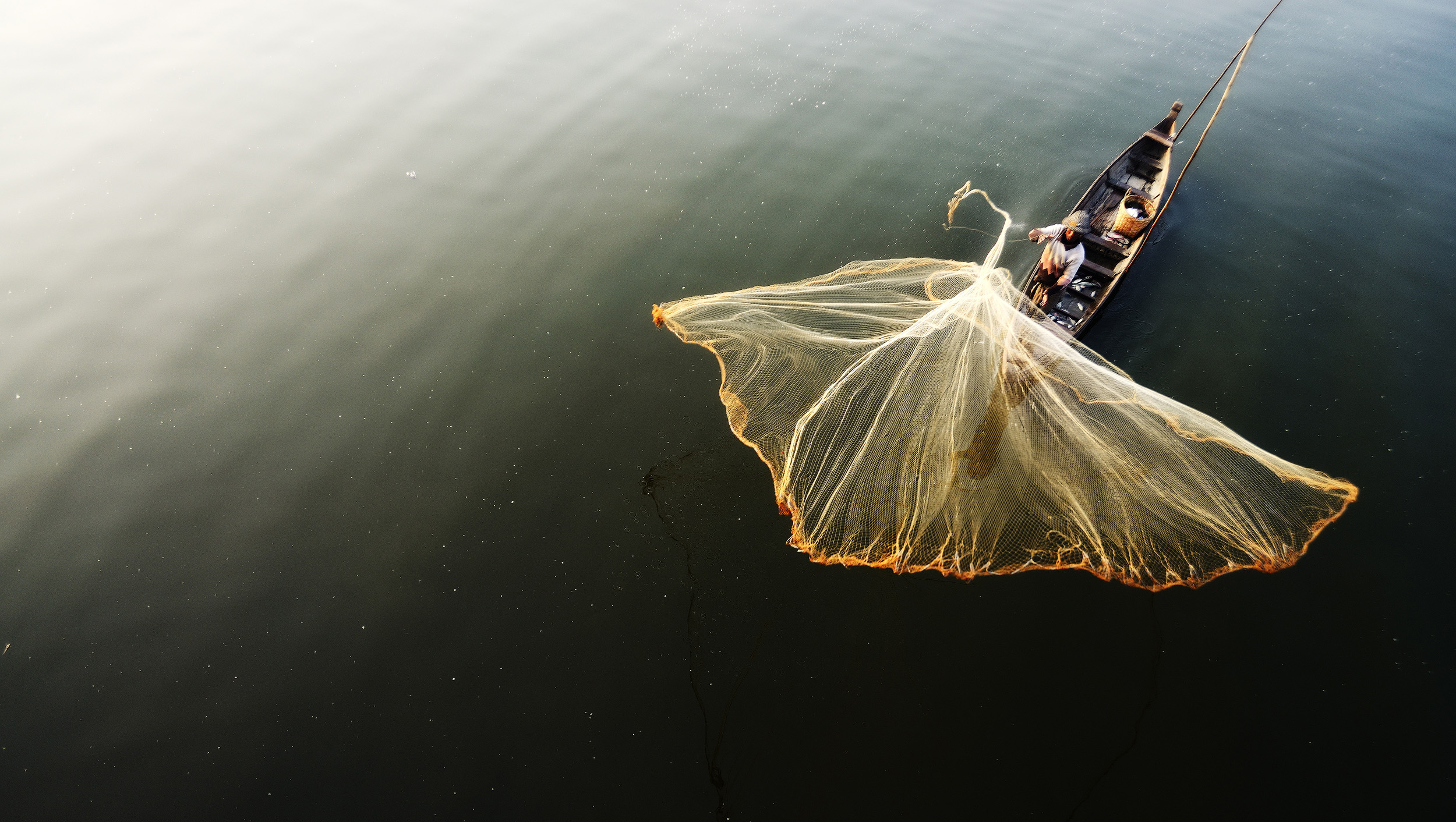 U Bein Fisherman   A fisherman casts his nets below U Bein bridge in Amarapura.