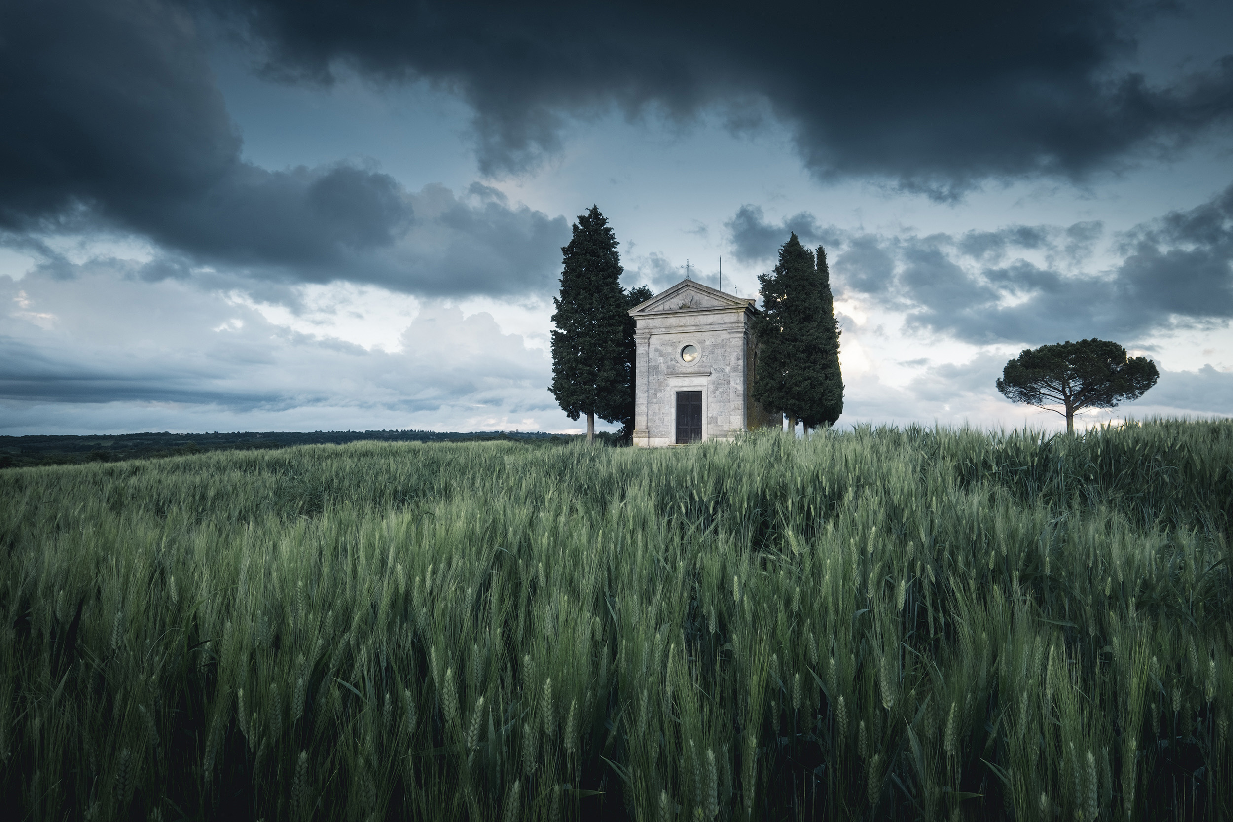 Cappella   The iconic Cappella della Madonna di Vitaleta standing atop one of the Val d'Orcia's hills in the last light of day beneath a stormy sky
