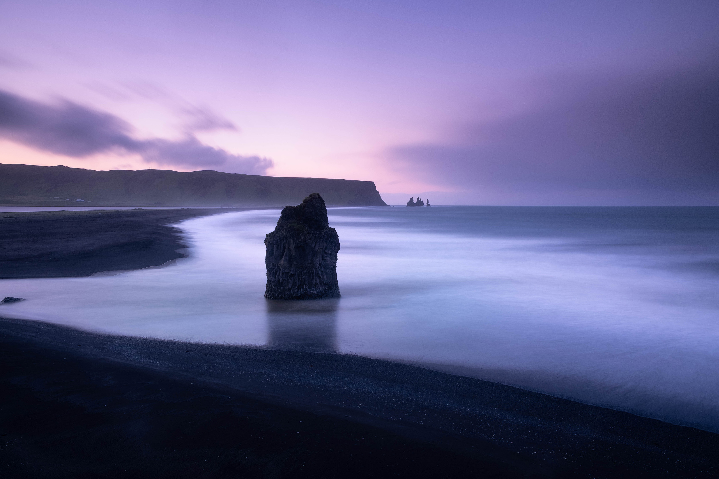 The long sweep of black sand on Reynisfjara beach seen from the rocks of Dyrhólaey