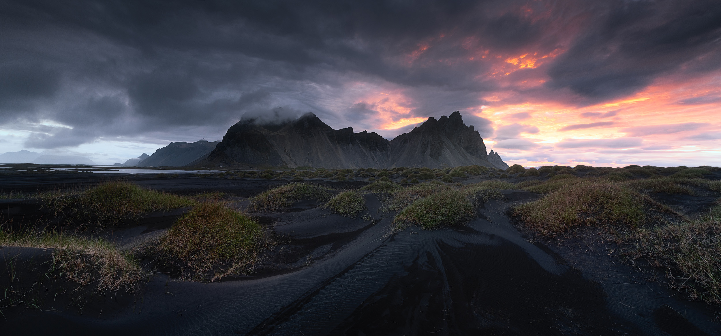 A panorama of the black sand dunes and jagged peaks of the Vestrahorn midway between sunset and sunrise.