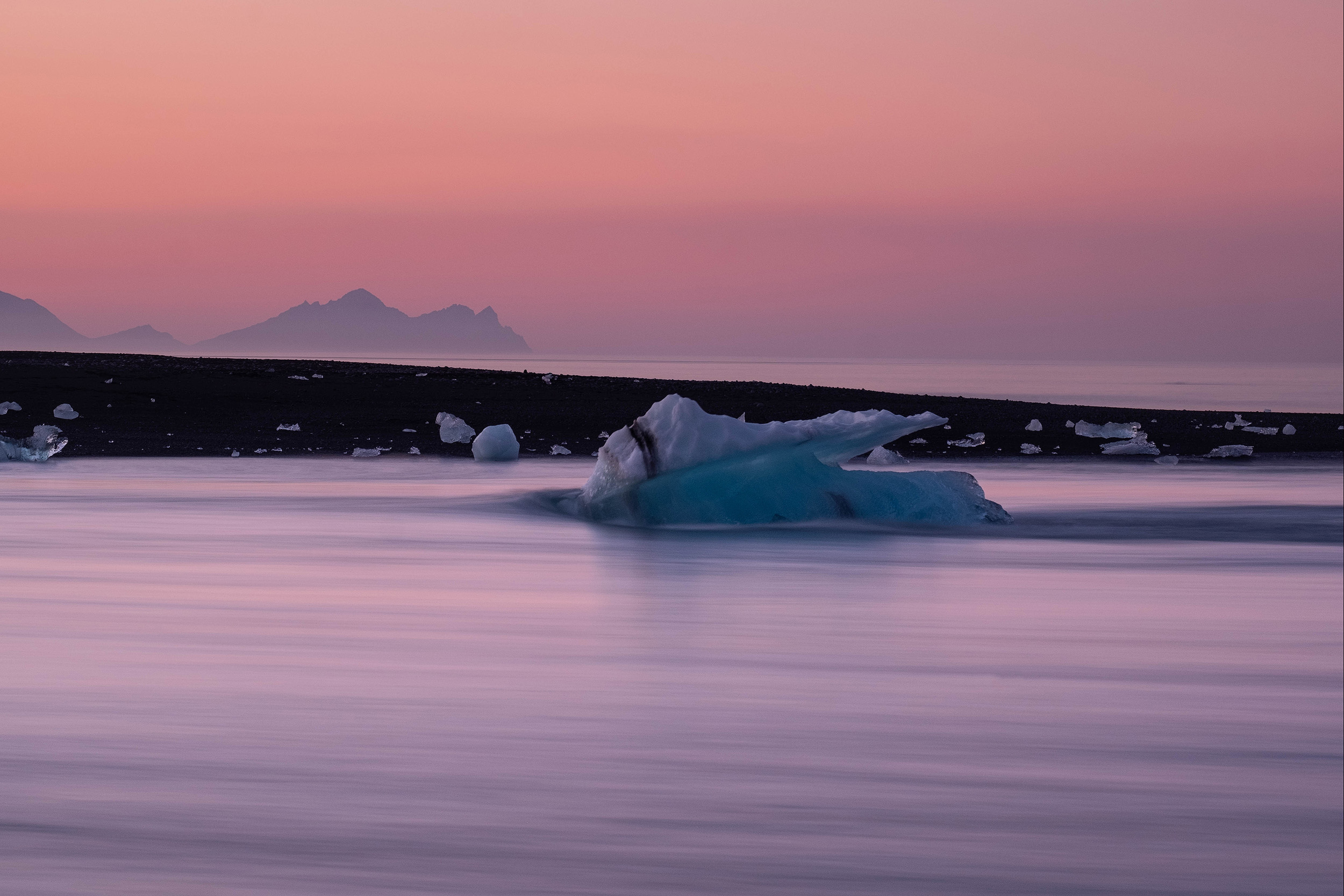 Icebergs washed up on the black sand beach at Jokulsarlon with the distant peaks of the Vestrahorn beyond.