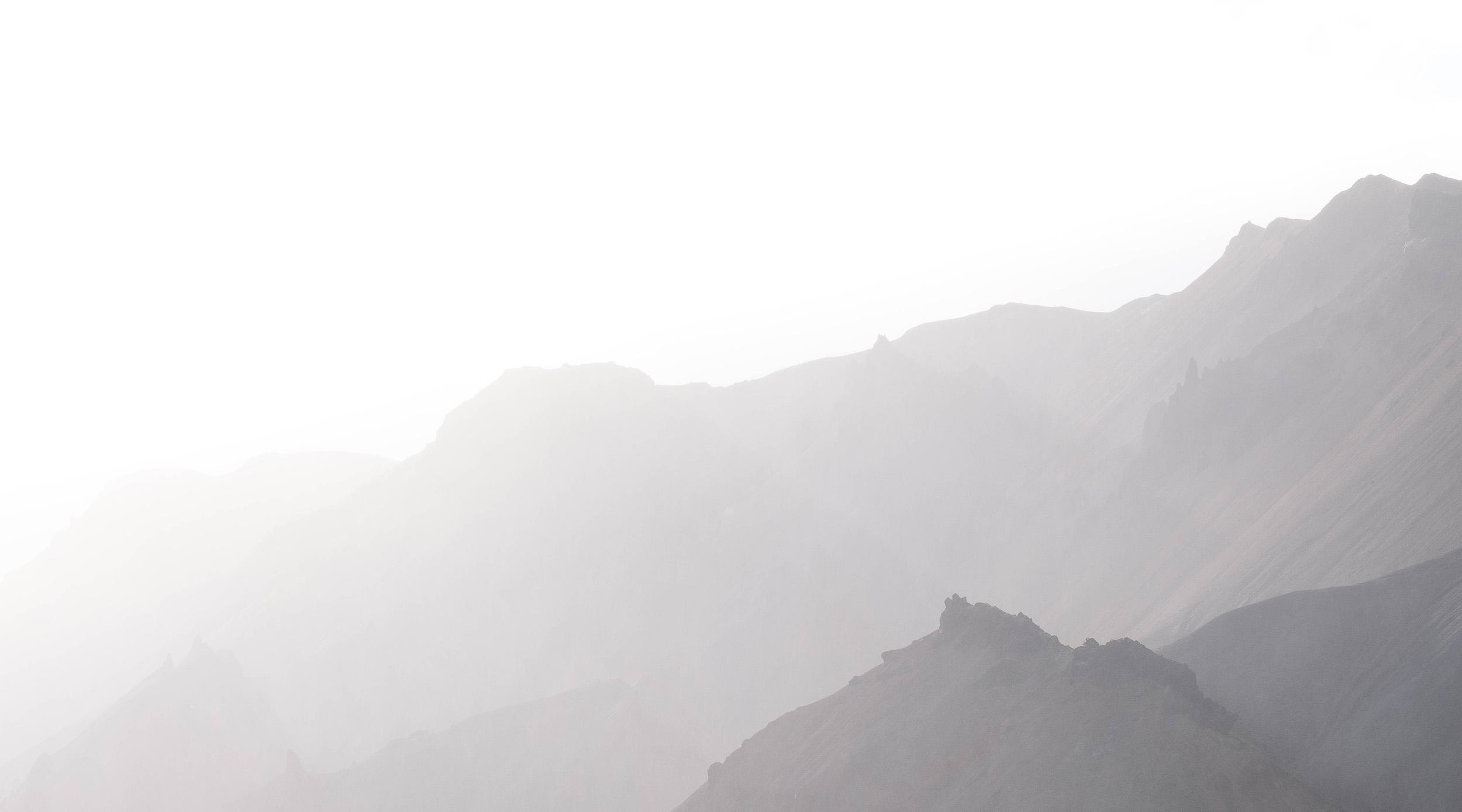 The peaks of Landmannalaugar backlit through a rainstorm.