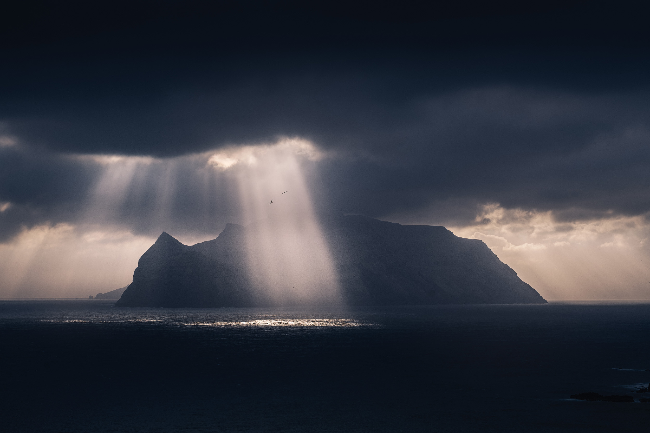 Bøur   Dramatic light breaks over the island of Mykines, captured from the small village of Bøur in the island of Vagar