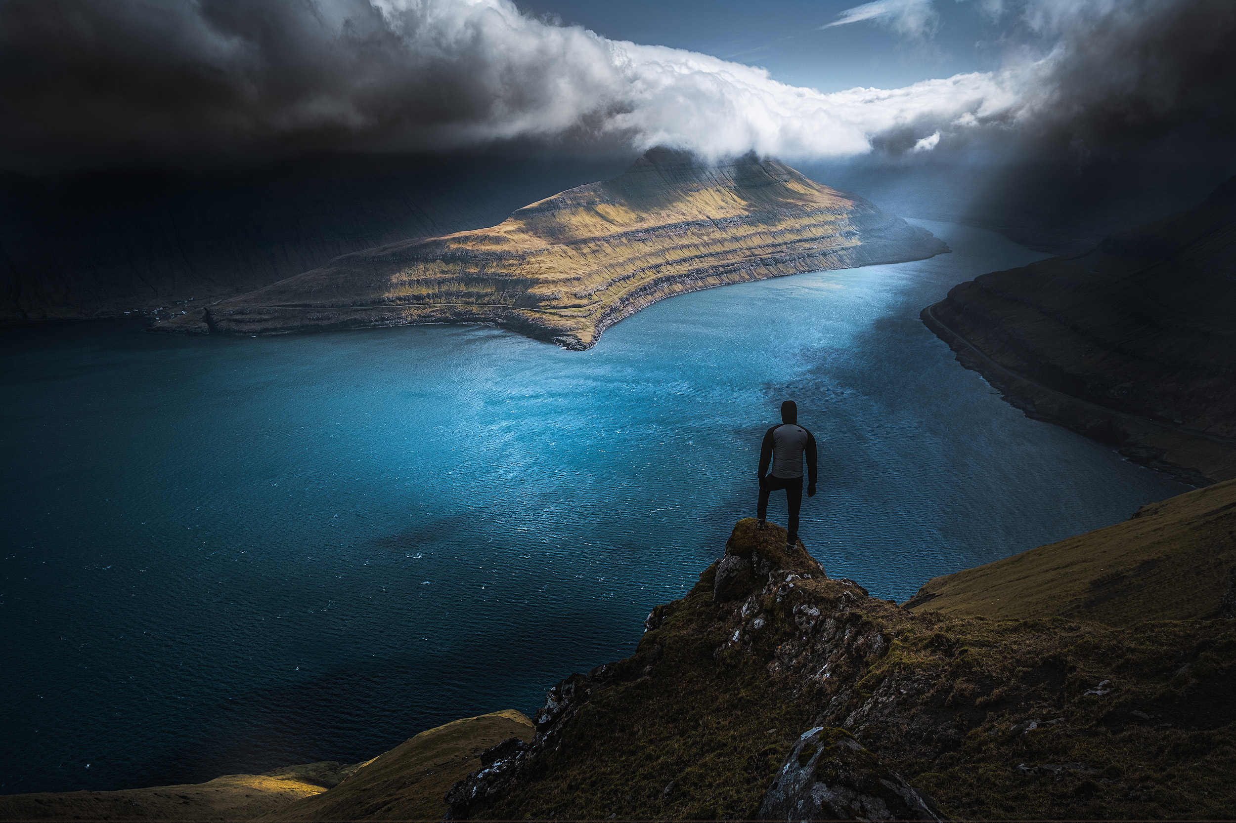 The view from above Funningsfjordur as light breaks through the heavy storm clouds. Andrea Livieri gives some scale to the scene.