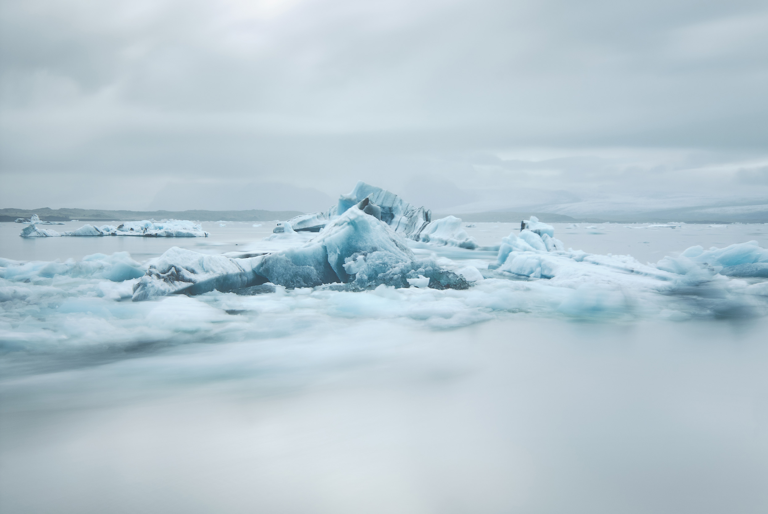 A long exposure blurs the smaller icebergs as the flow the the sea while the larger pieces remain caught on the bottom of the lagoon.