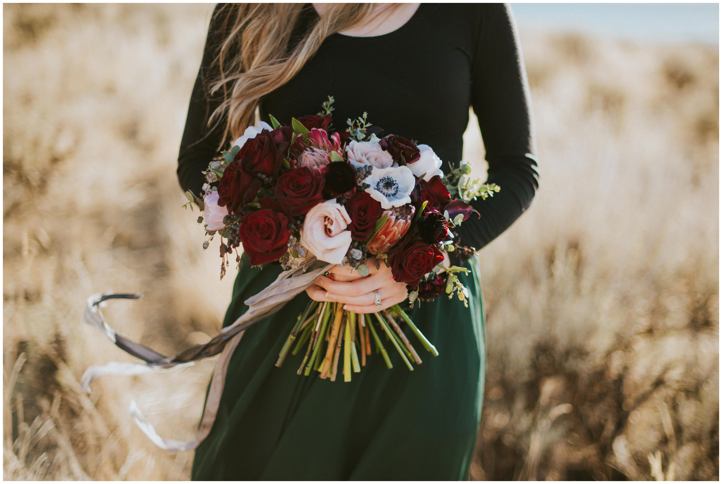 Bride holding bouquet with red roses, blush roses, grey ribbon, and emerald green skirt  | Wedding Photographer Bear Lake Utah www.riversandroadsphotography.com
