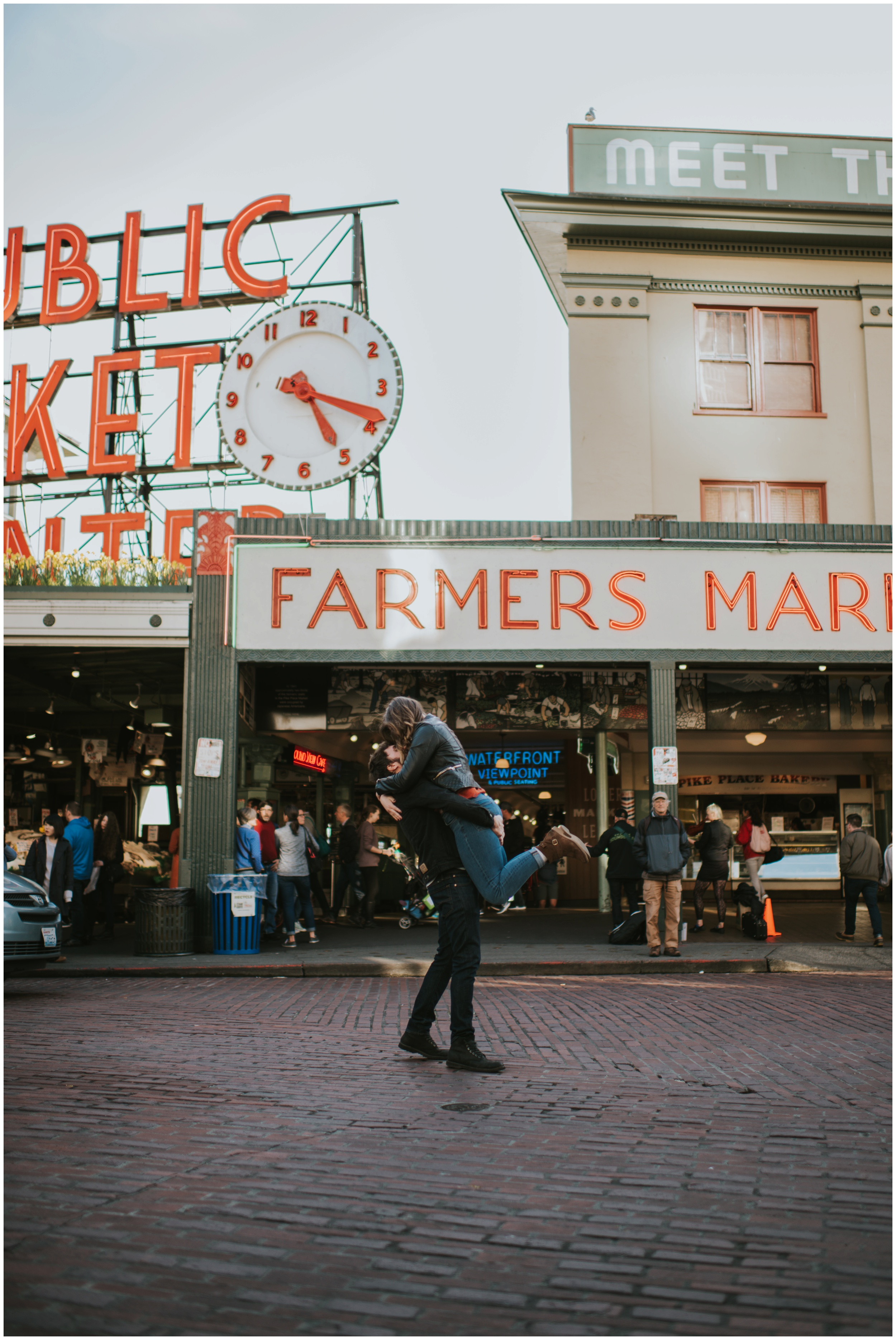 Guy picking girl up in the middle of the street in Seattle  | Seattle Engagement Photographer www.riversandroadsphotography.com