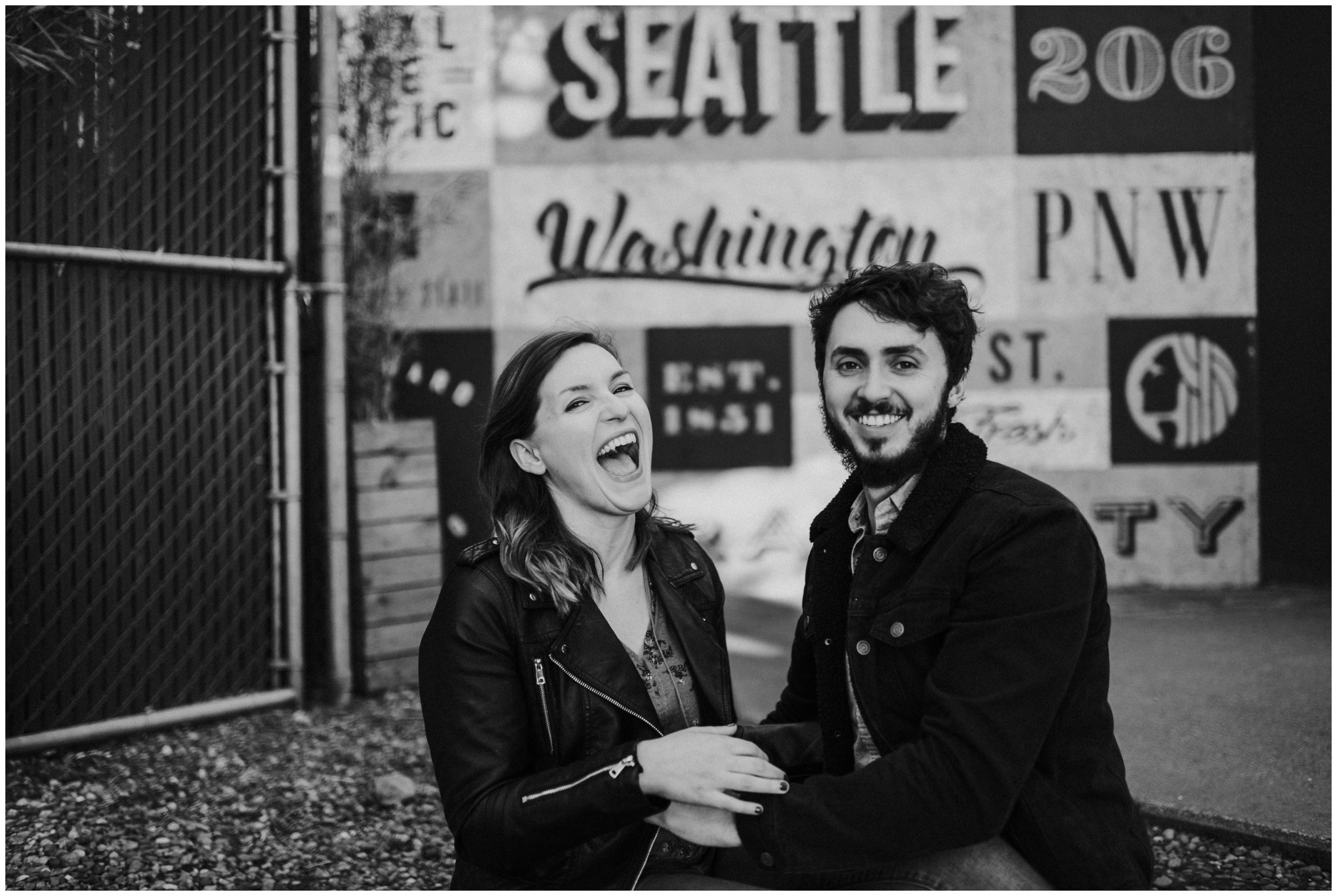 Black and white photo of couple laughing in Downtown Seattle  | Seattle Engagement Photographer www.riversandroadsphotography.com