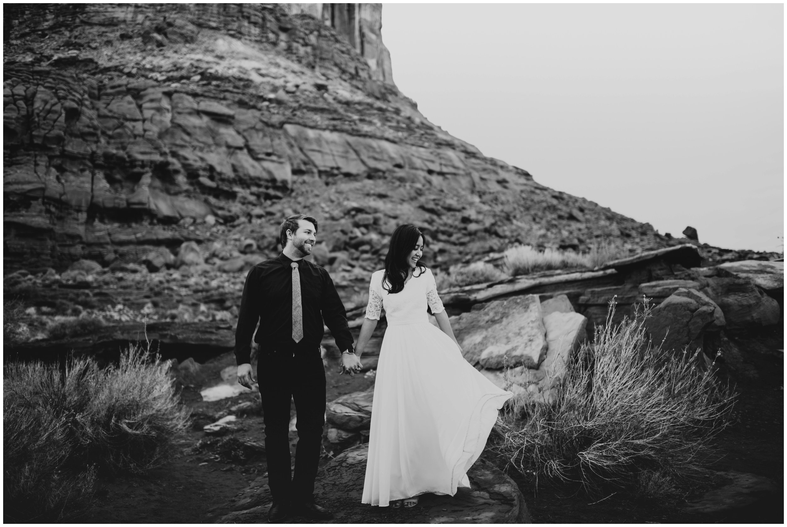 Groom looking at bride while bride plays with her dress while standing on rocks | Moab Utah, Photographer www.riversandroadsphotography.com