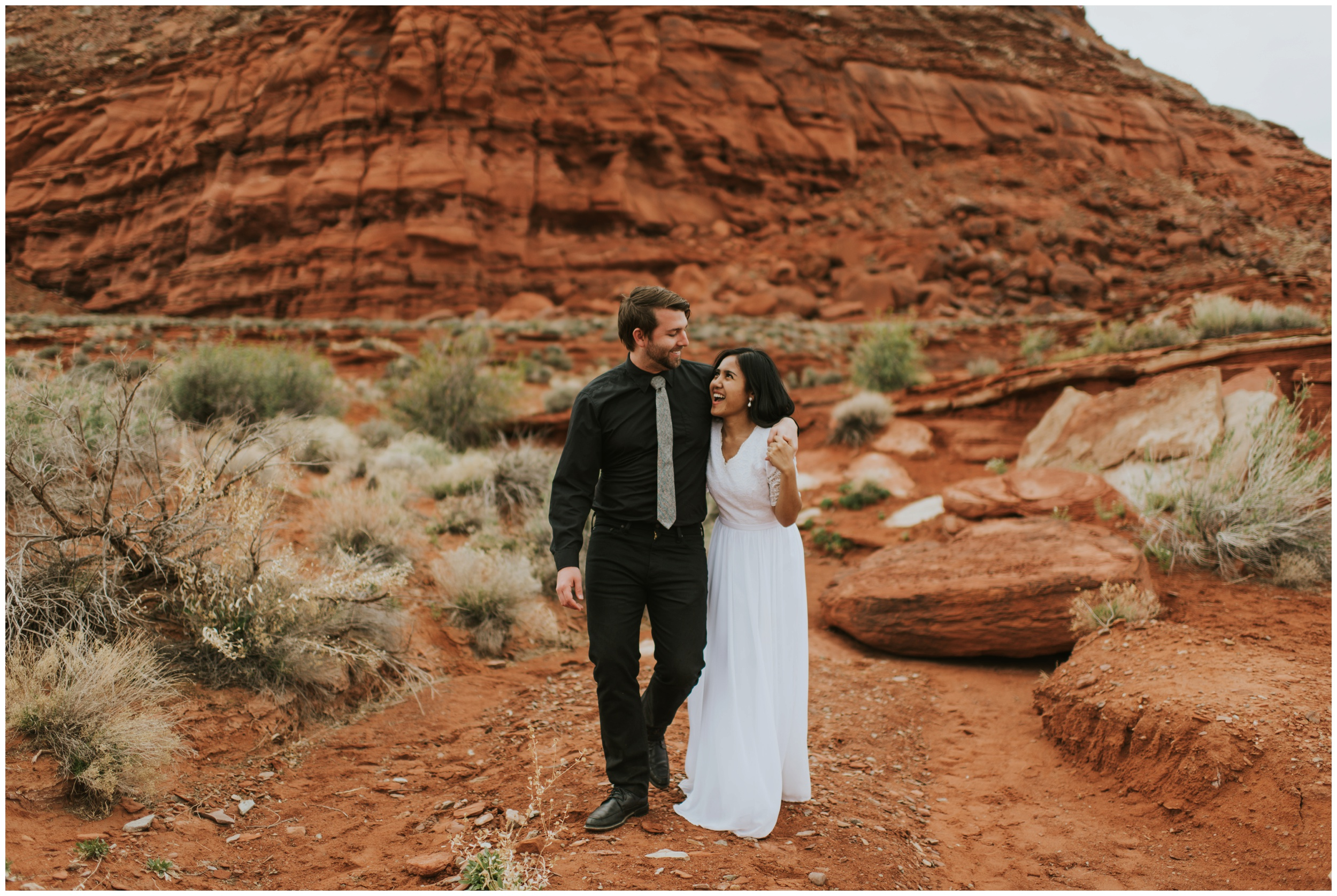 Bride + Groom walking and laughing in a canyon. |Moab Utah, Photographer www.riversandroadsphotography.com