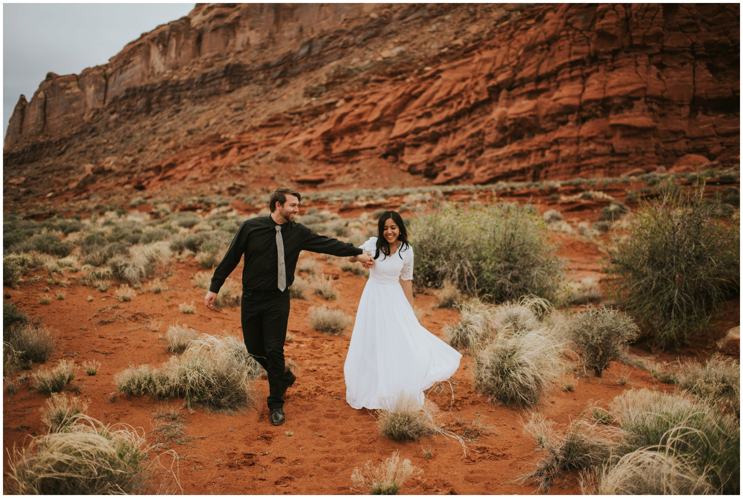 Bride and groom dancing and playing in a canyon  | Moab Utah, Photographer www.riversandroadsphotography.com
