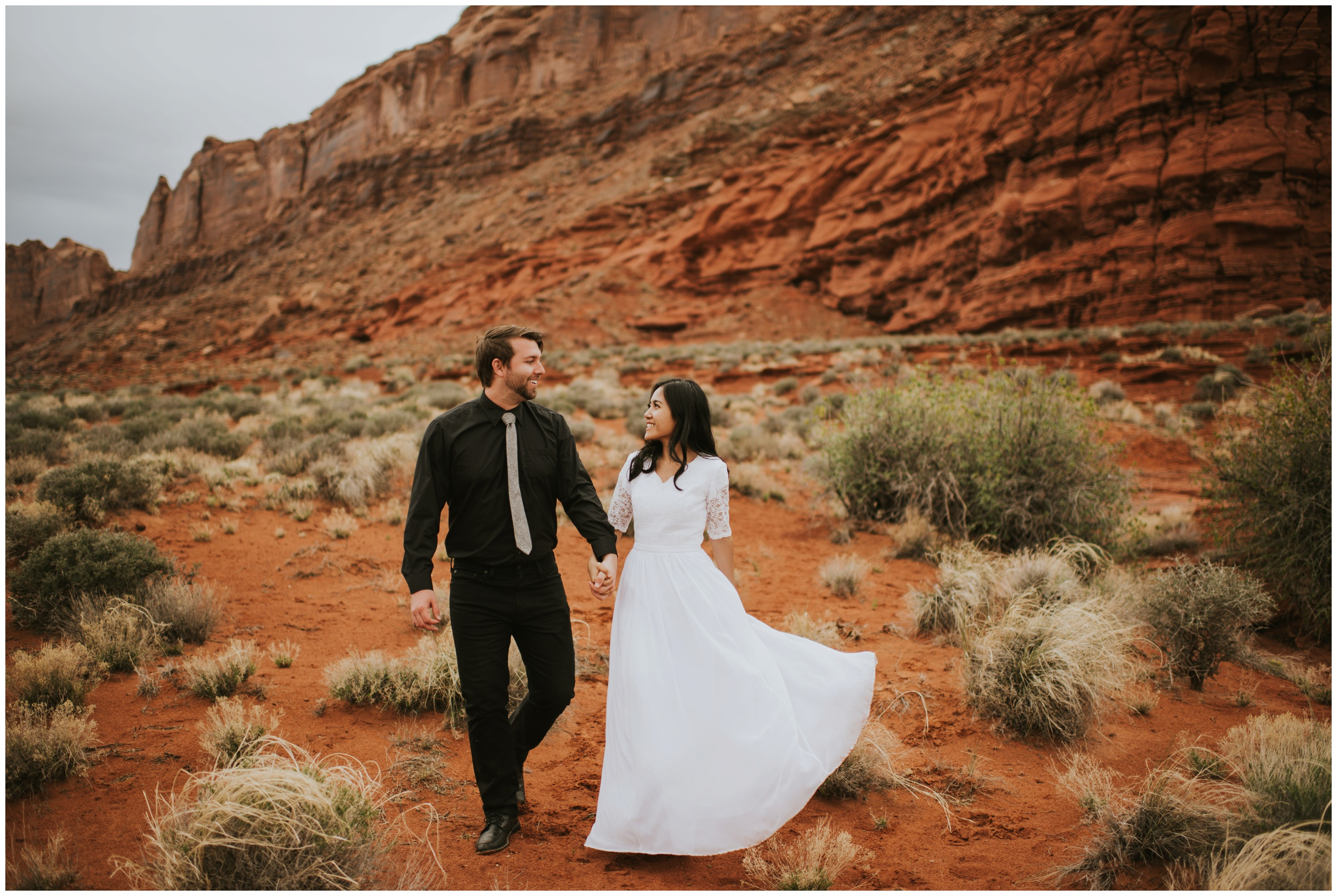 Couple holding hands and looking at each other, destination elopement, candid photography  | Moab Utah, Photographer www.riversandroadsphotography.com