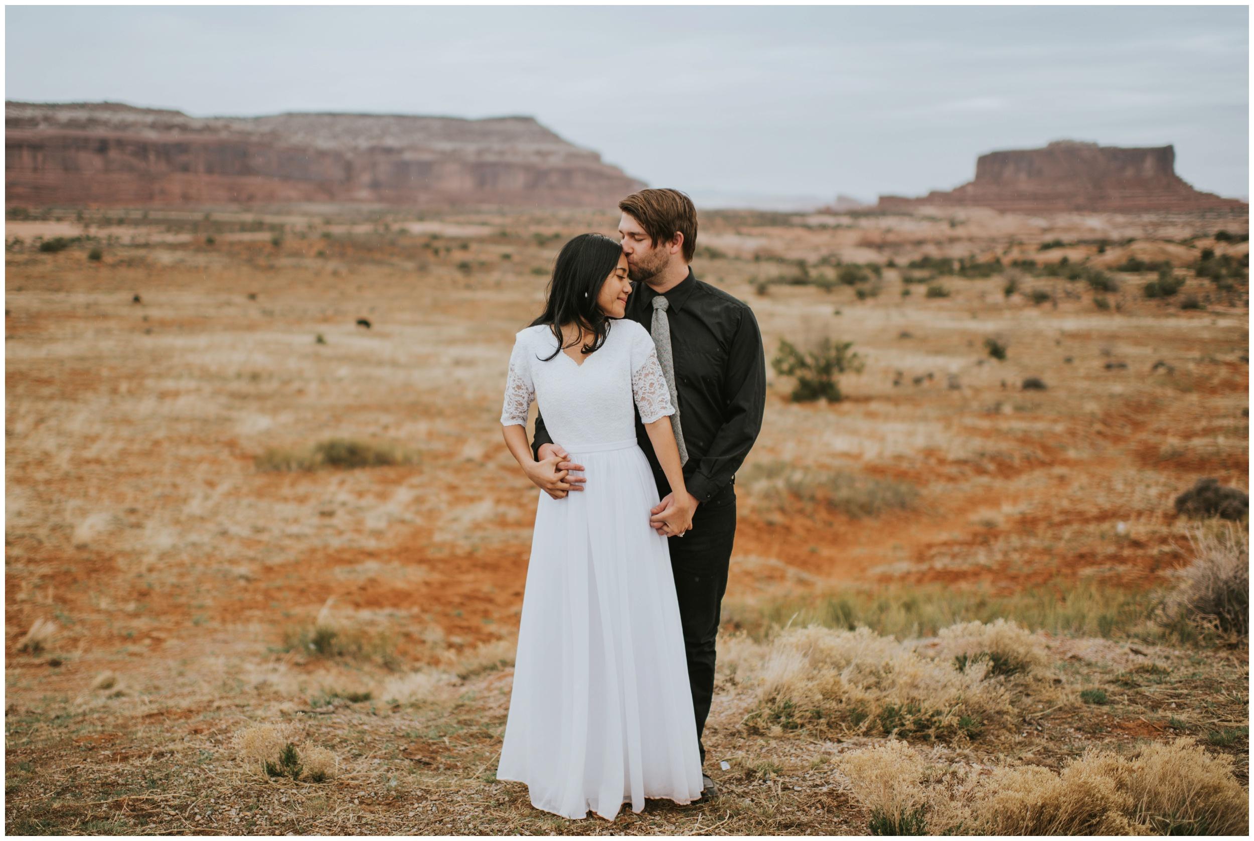 Tender moment during bridal portraits of groom kissing brides forehead |Moab Utah, Photographer www.riversandroadsphotography.com