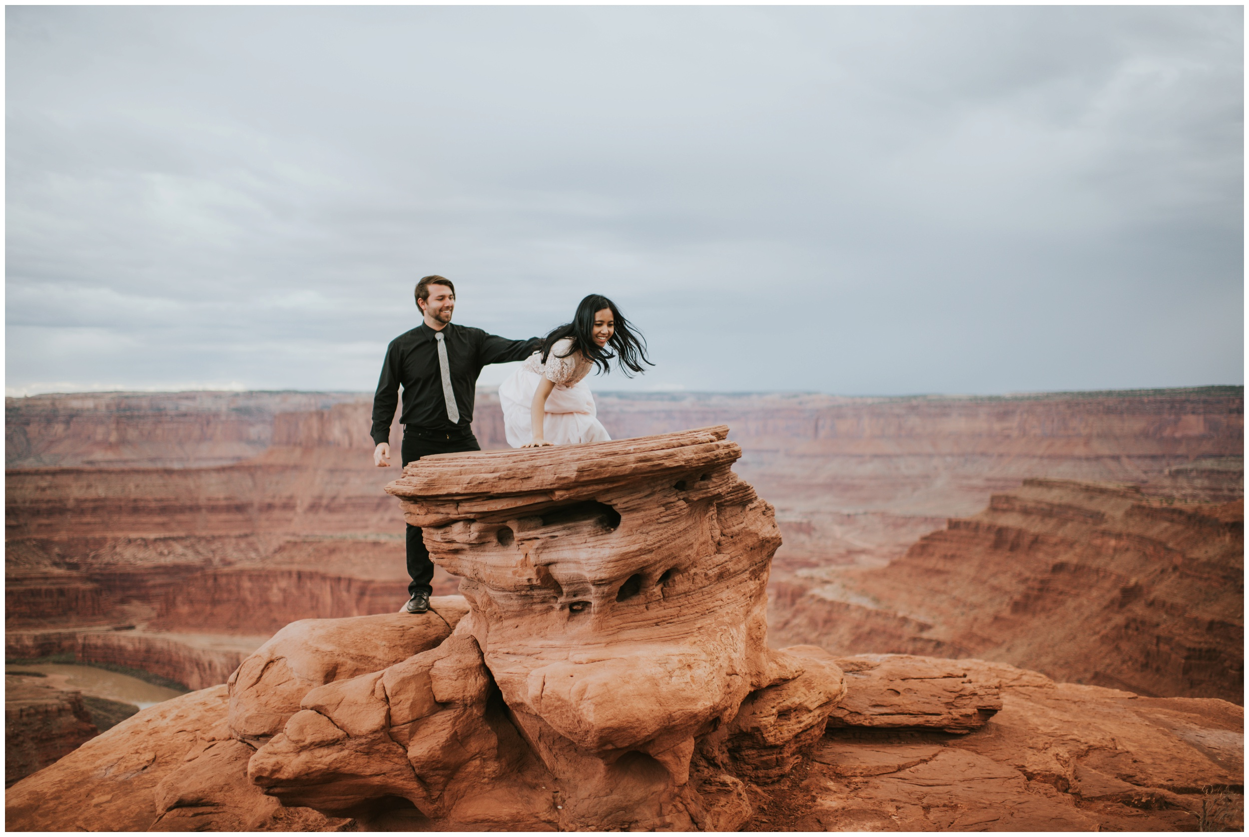 Couple climbing rocks at dead horse point in Moab utah | Elopement Photographer www.riversandroadsphotography.com