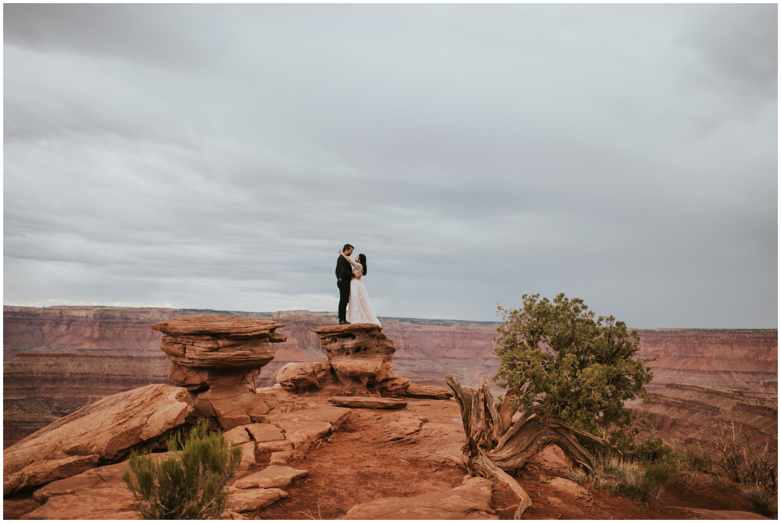Portrait or bride and groom on a cliff eloping at Dead Horse Point | Elopement Photographer www.riversandroadsphotography.com