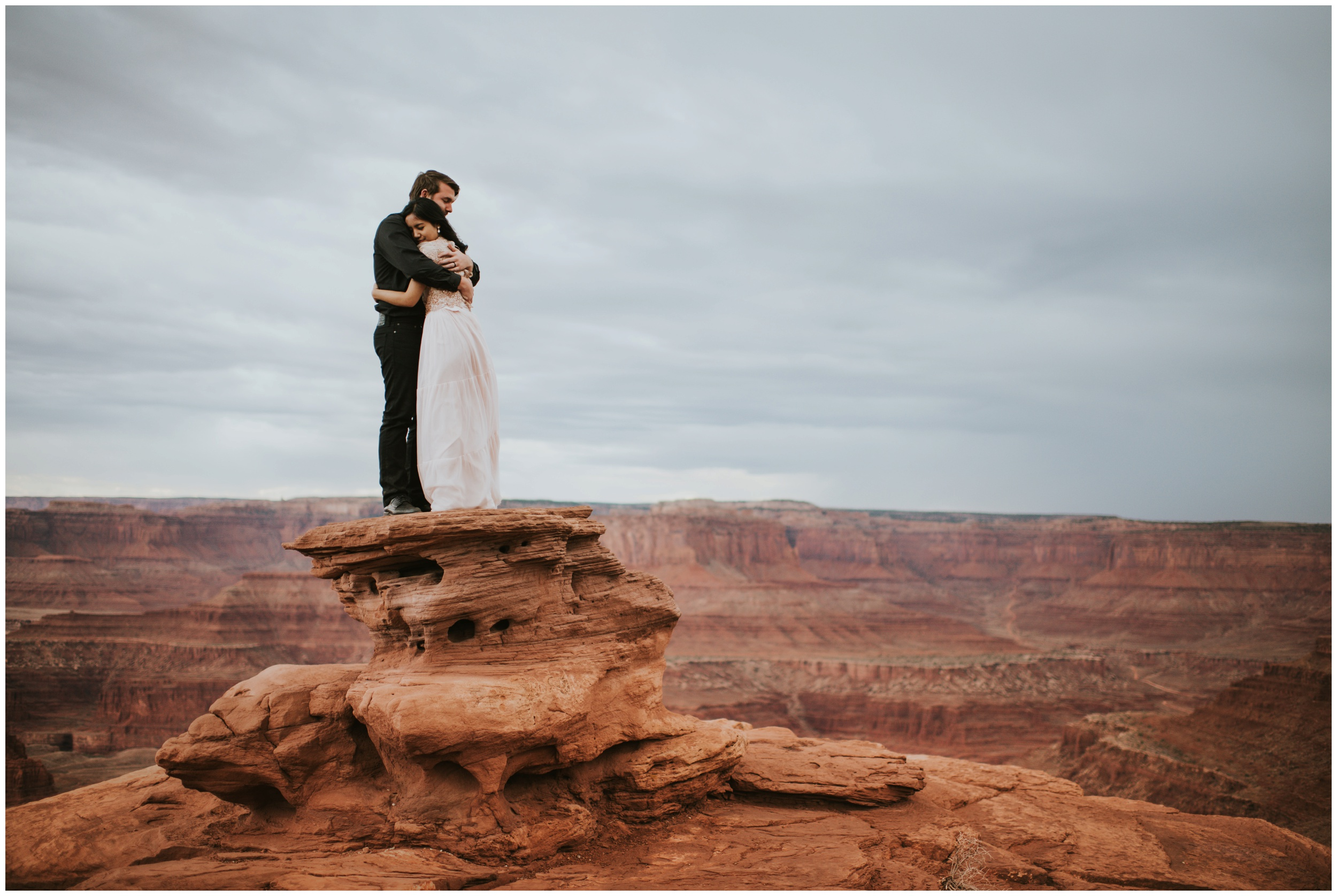 Bride and Groom hugging ontop of Dead Horse Point Overlook | Elopement Photographer www.riversandroadsphotography.com