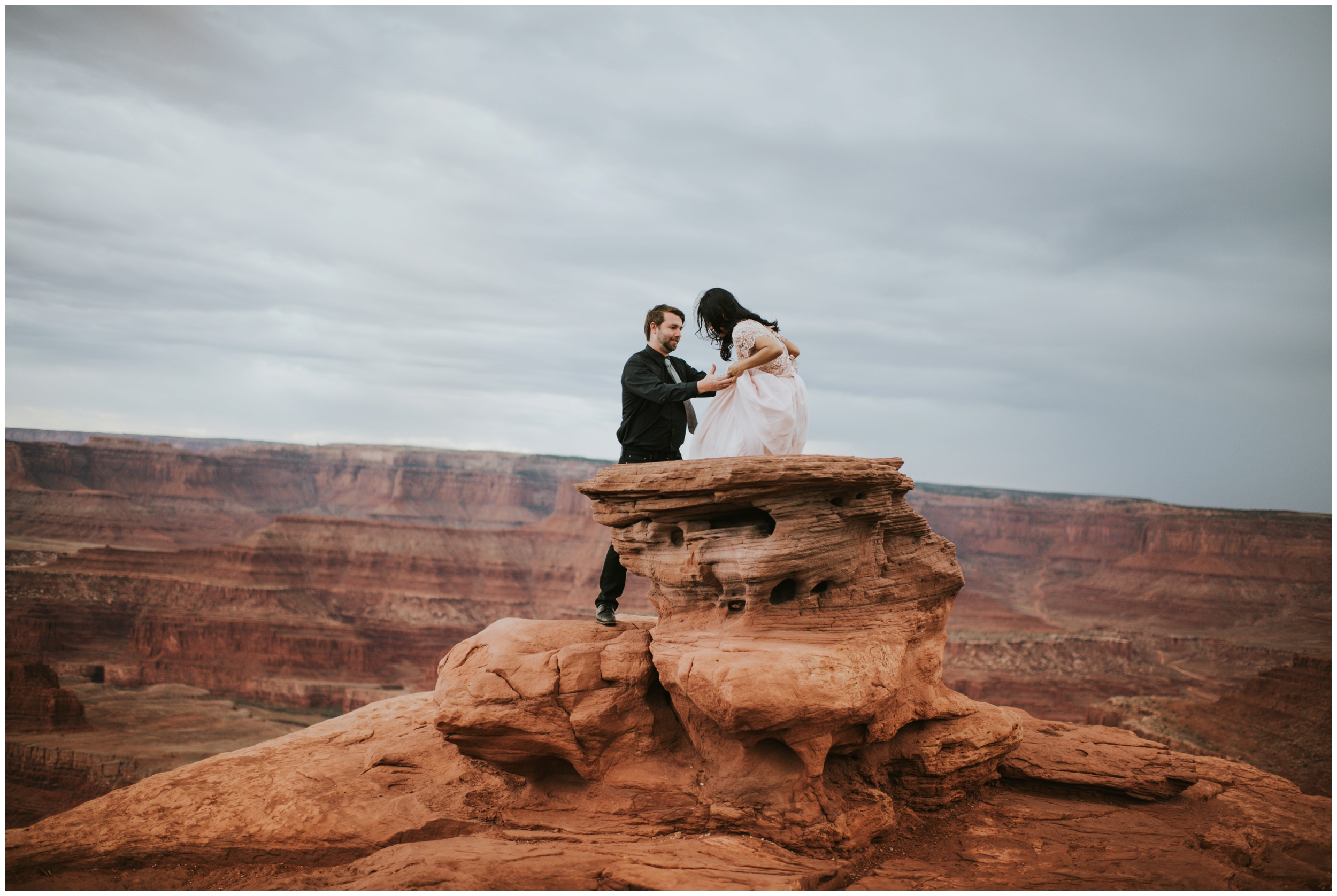 Couple climbing at dead horse point overlook | Elopement Photographer www.riversandroadsphotography.com