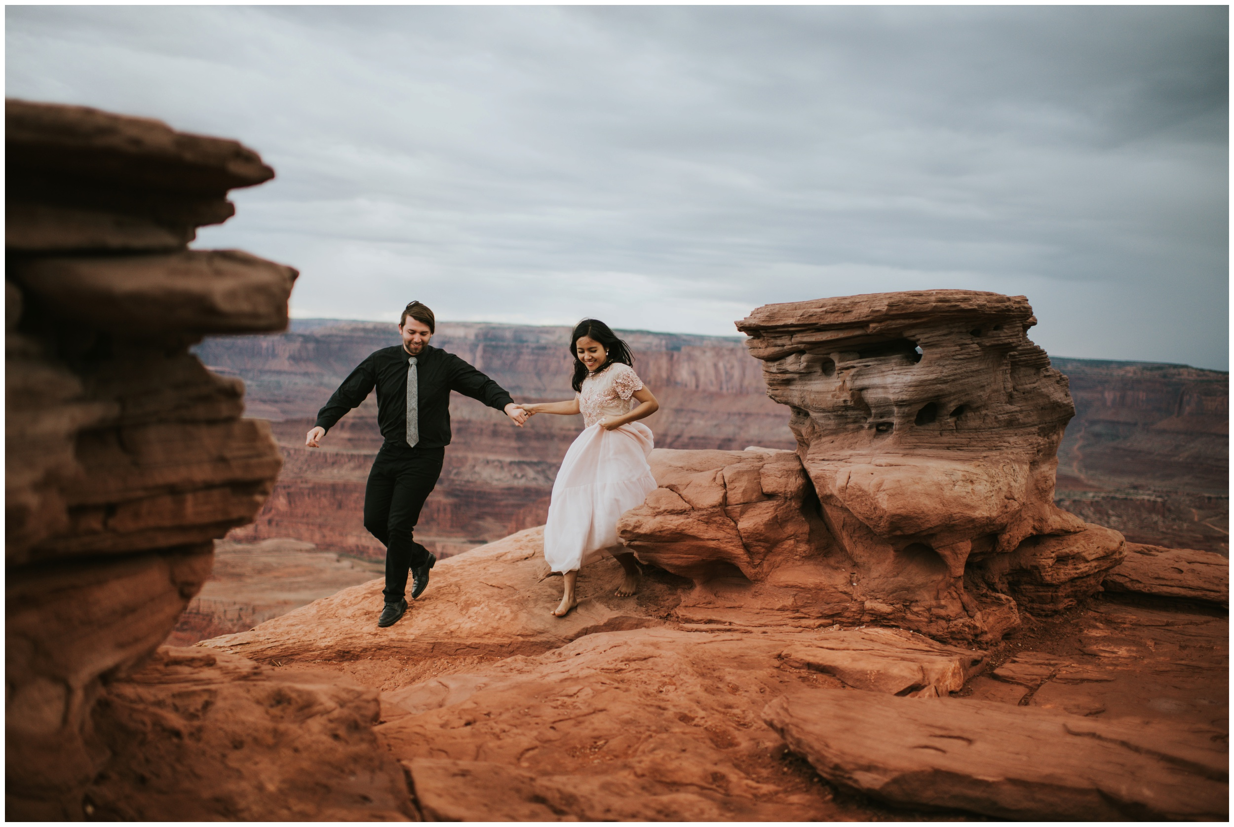 couple running together after eloping at Dead horse point state park | Elopement Photographer www.riversandroadsphotography.com