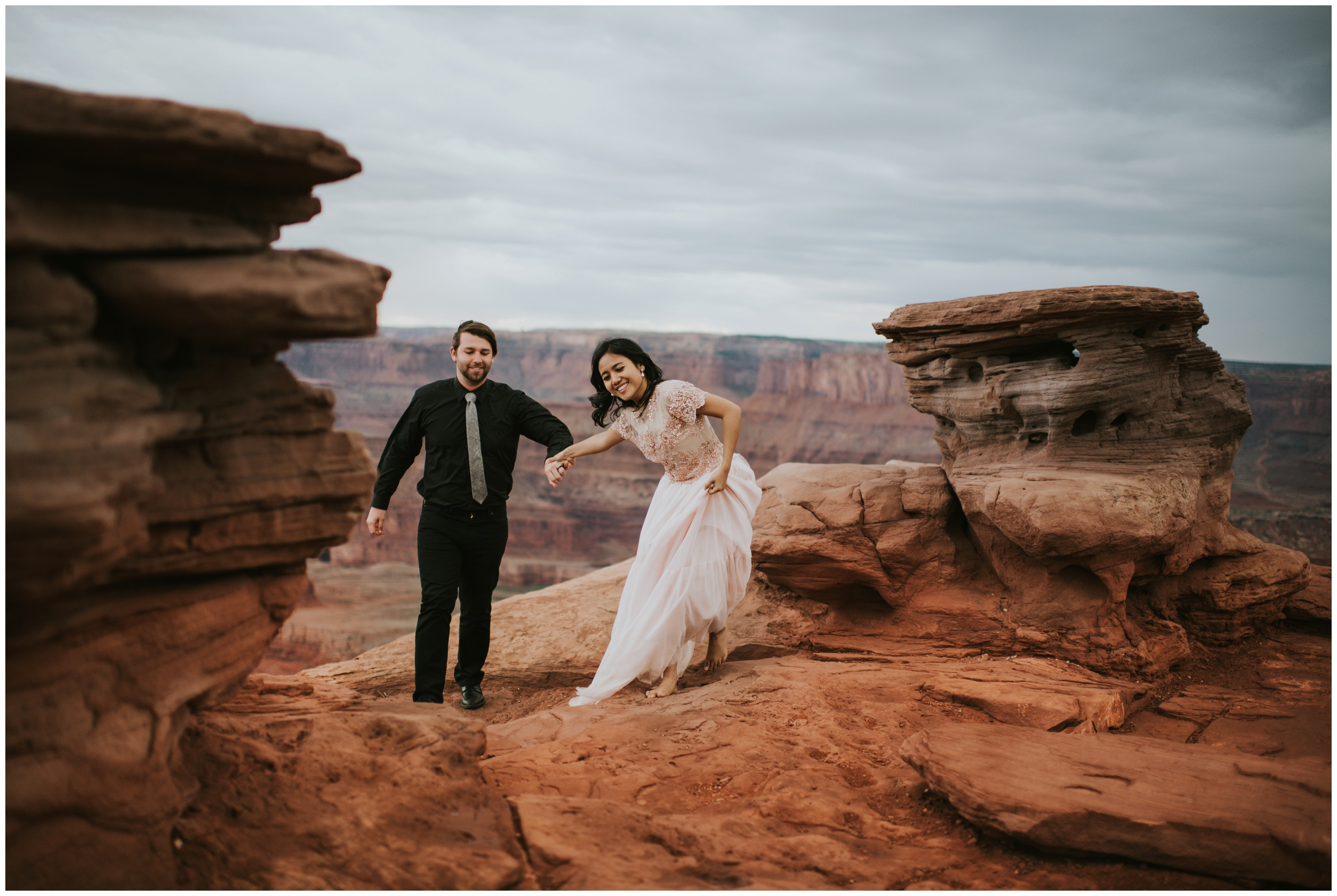 Couple running and laughing ontop of dead horse point state parks overlook | Elopement Photographer www.riversandroadsphotography.com