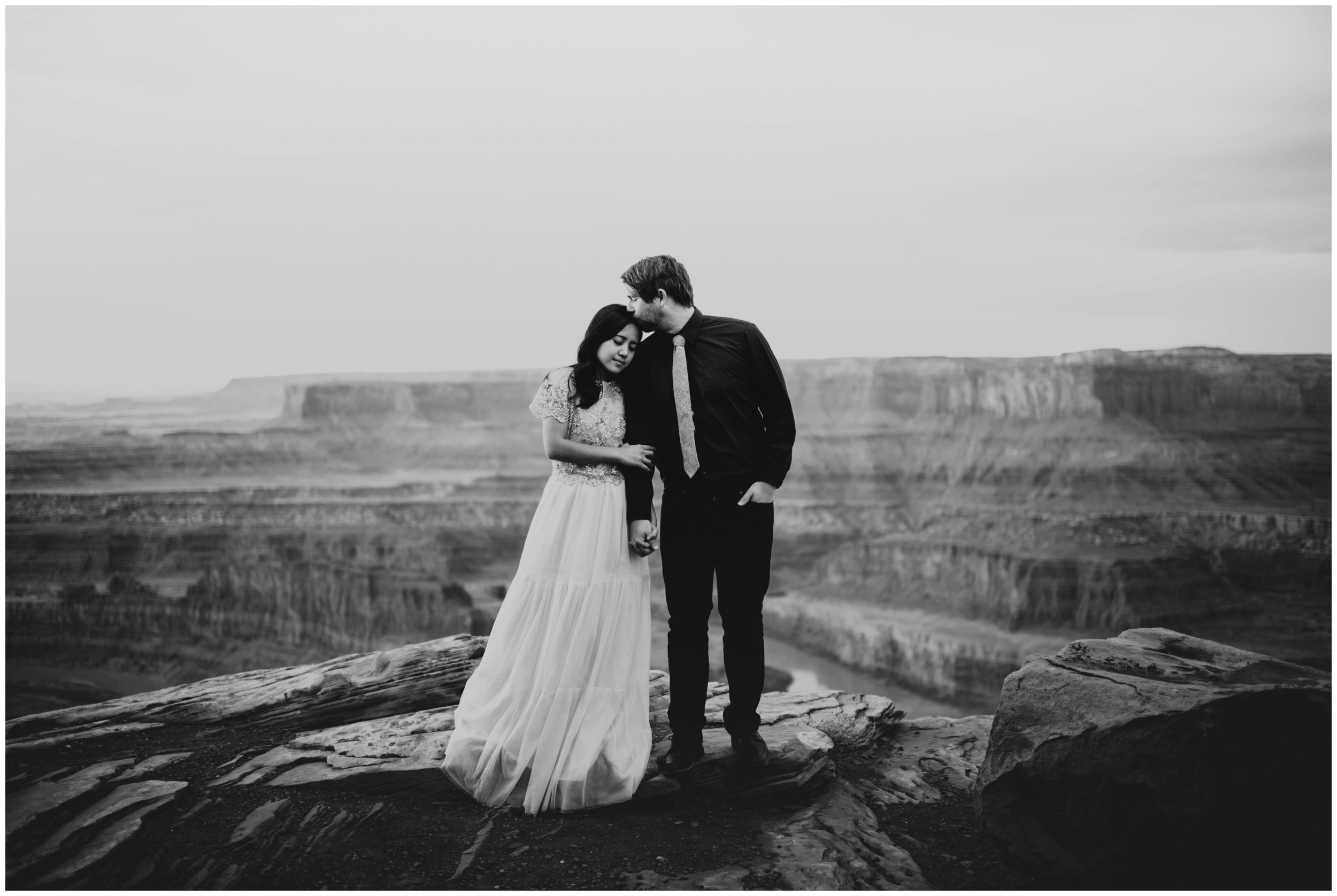 Black and white portrait of groom kissing brides forehead at Dead Horse Point State Park | Elopement Photographer www.riversandroadsphotography.com