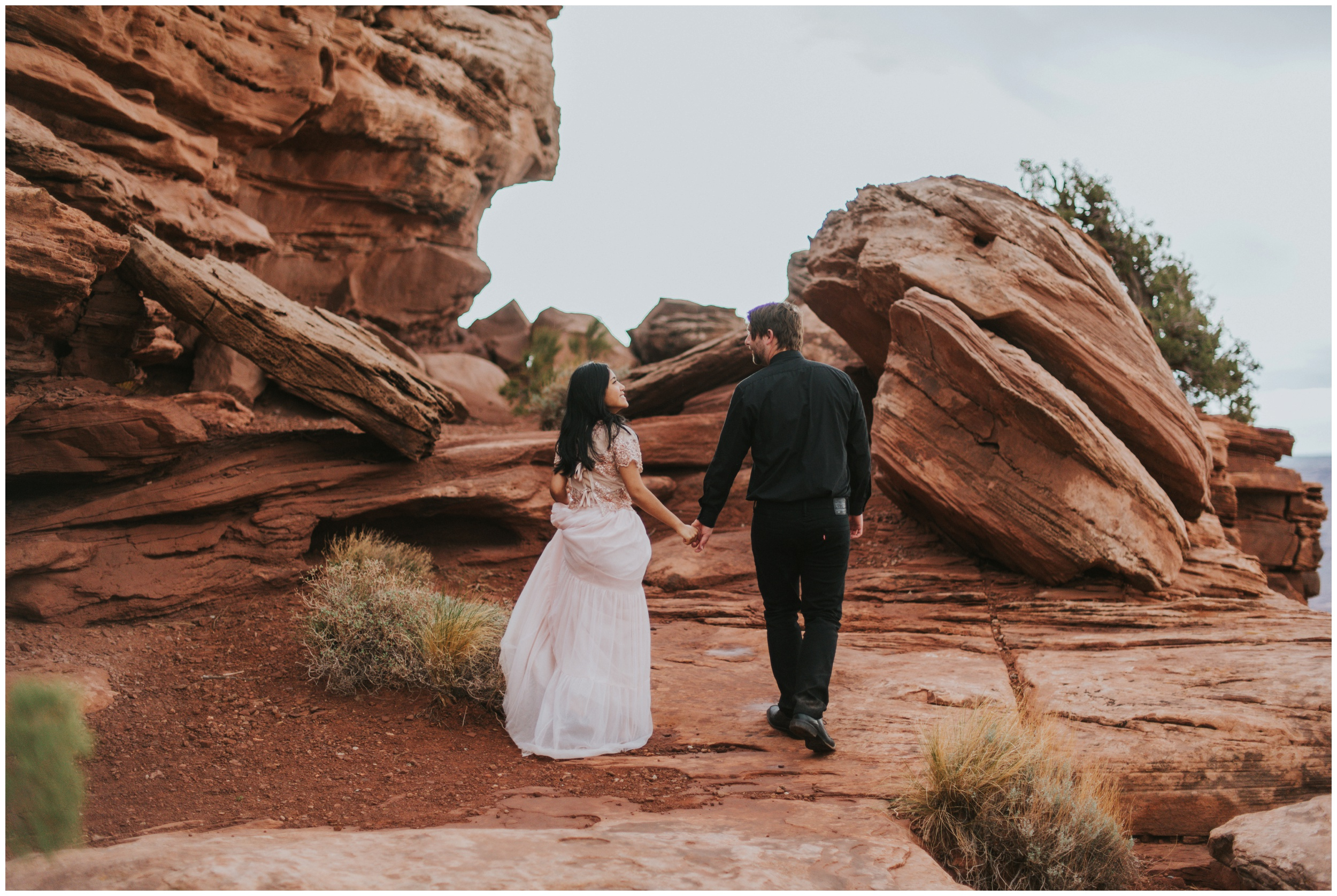 Couple holding hands and walking away from the camera after eloping at Dead Horse Point State Park Overlook | Elopement Photographer www.riversandroadsphotography.com