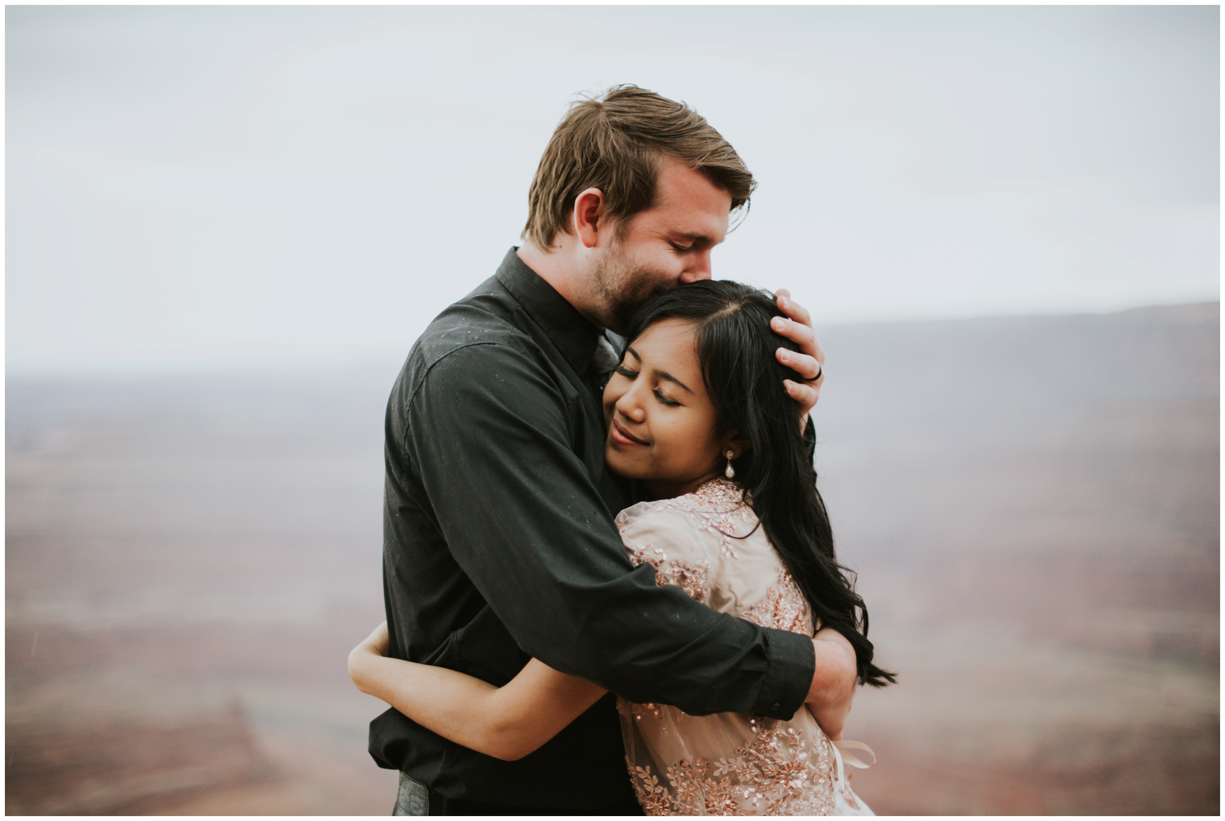 Couple hugging in the rain at Dead Horse Point State Park Overlook | Elopement Photographer www.riversandroadsphotography.com