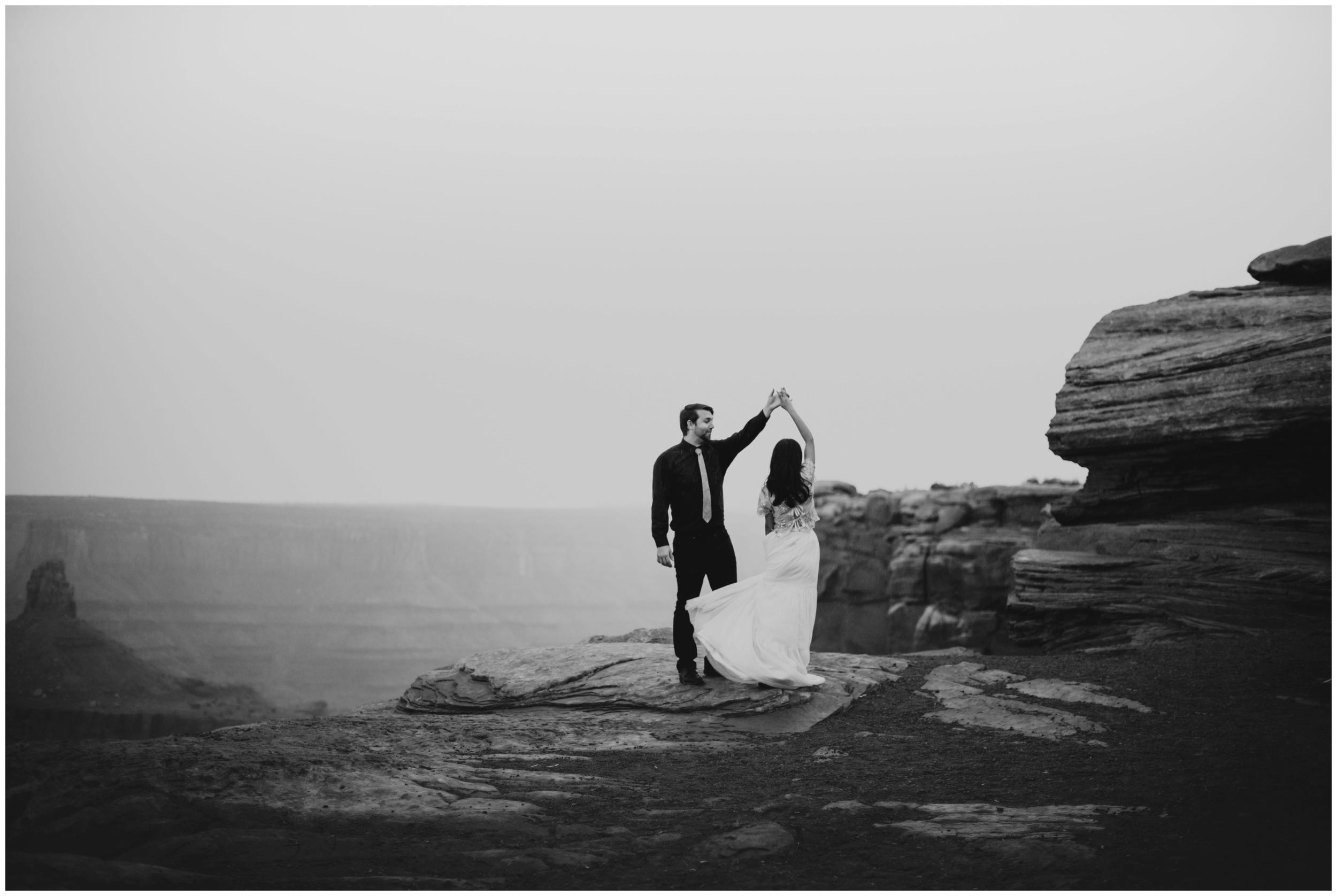 couple dancing on the rocks at dead horse point overlook | Elopement Photographer www.riversandroadsphotography.com